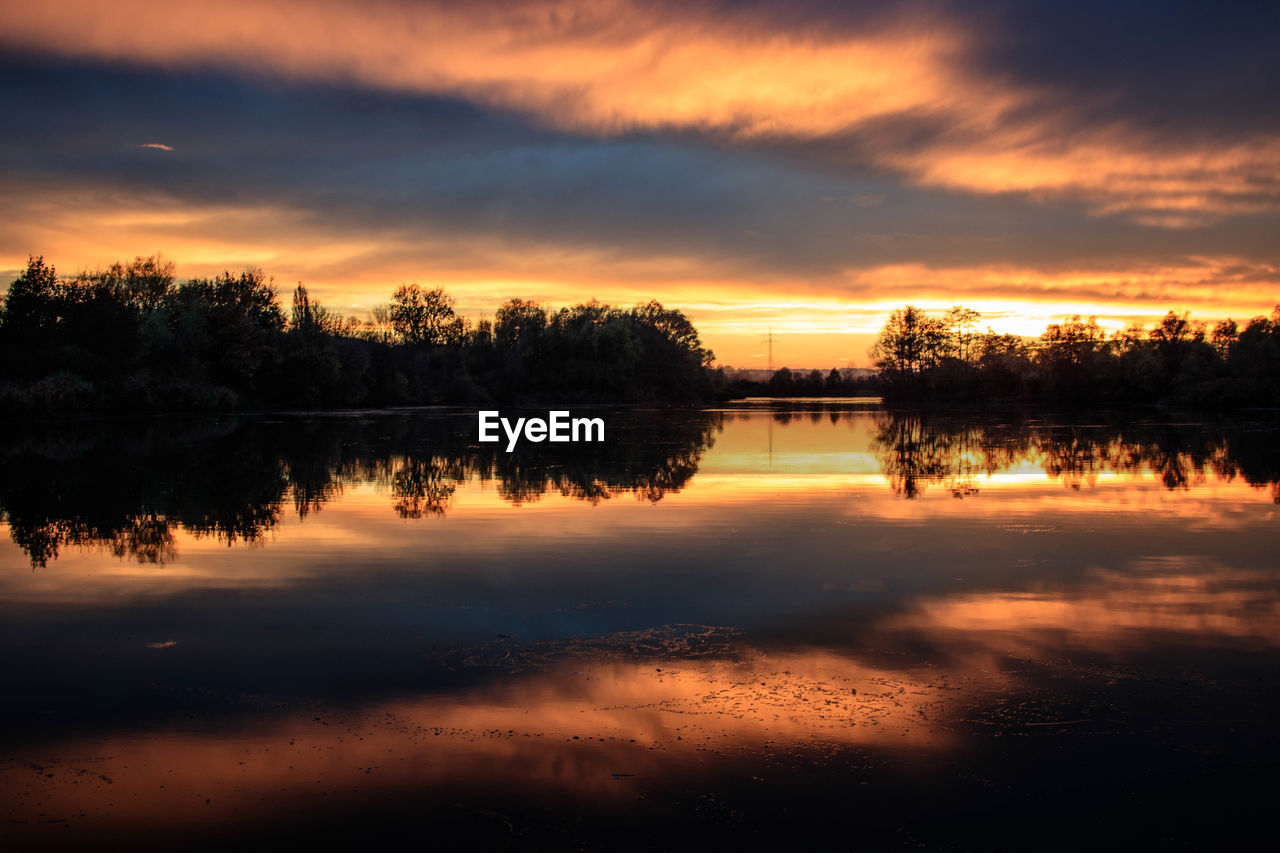 sunset, sky, reflection, cloud - sky, tranquility, water, scenics - nature, tranquil scene, beauty in nature, orange color, lake, tree, idyllic, plant, silhouette, nature, no people, waterfront, non-urban scene, outdoors, reflection lake