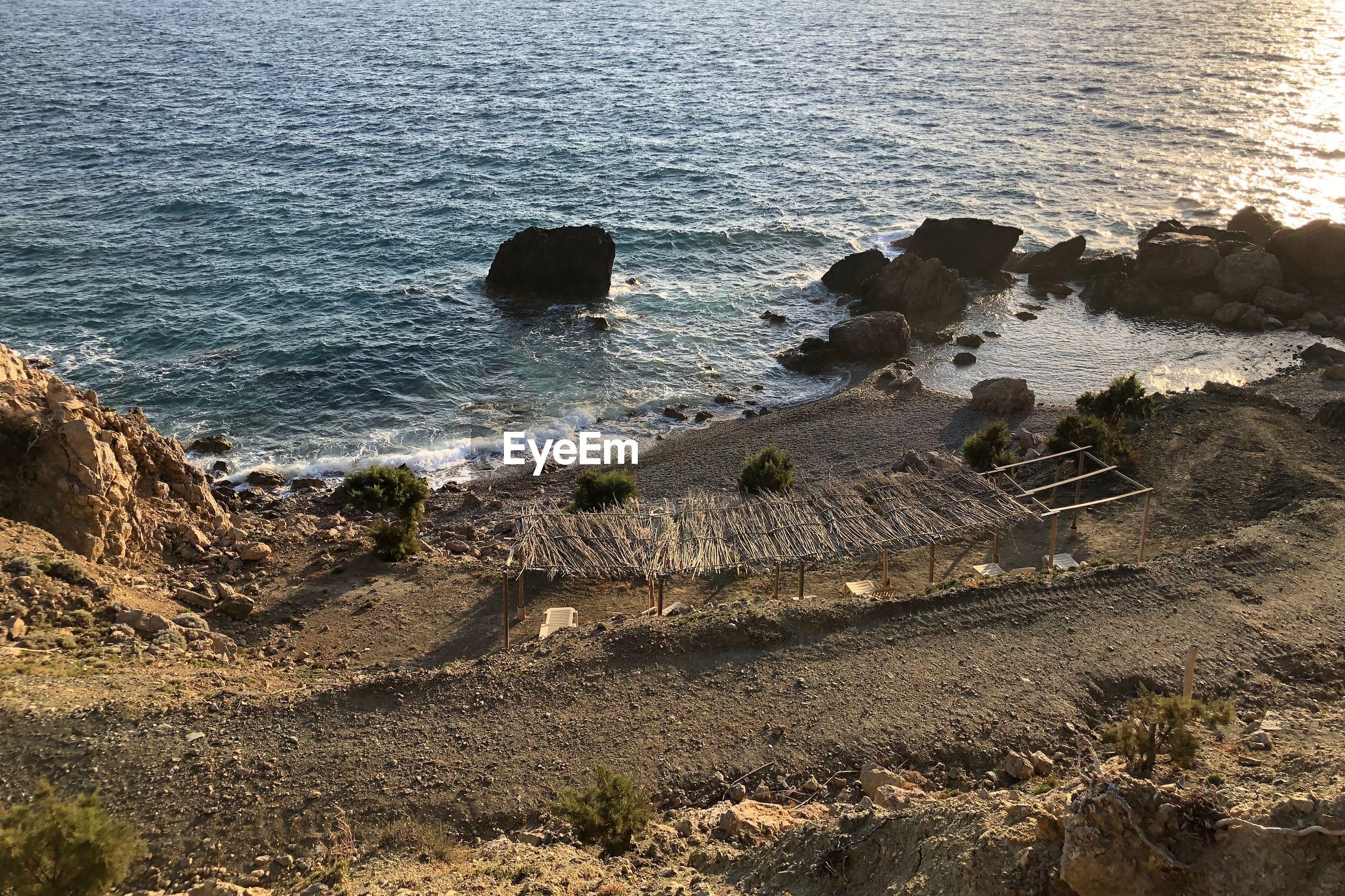 HIGH ANGLE VIEW OF ROCKS ON SHORE AT SEA