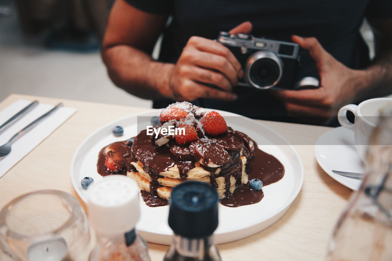 Midsection Of Man With Camera Sitting By Pancake In Plate On Table At Restaurant