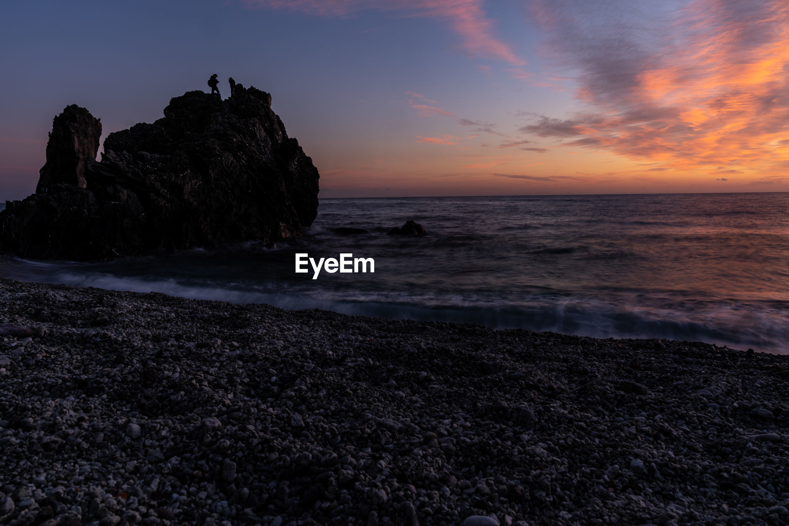 SCENIC VIEW OF ROCKS AT SUNSET