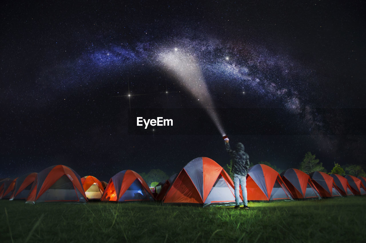 Rear view of man holding flashlight while standing by tents against star field