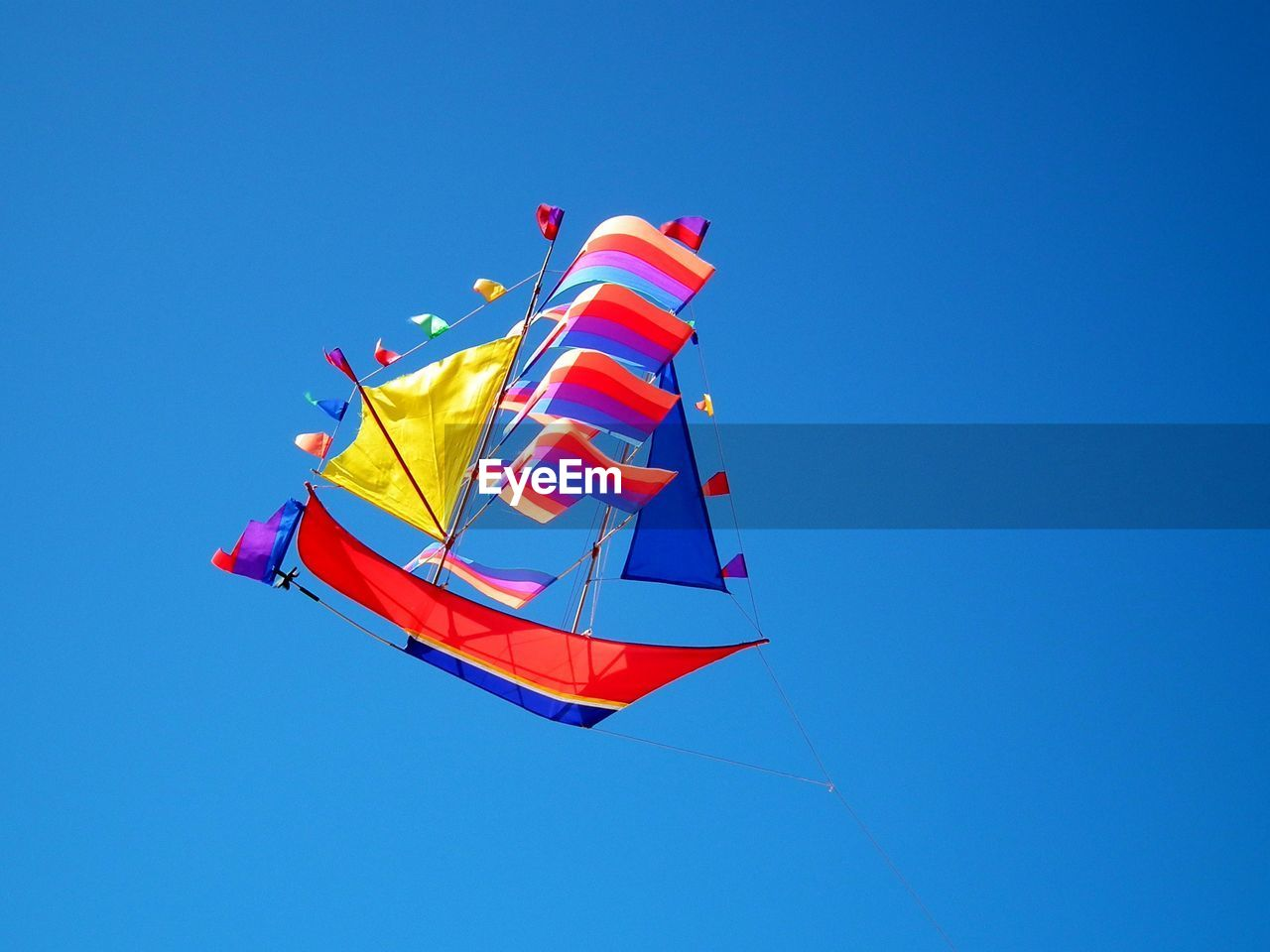 sky, blue, clear sky, low angle view, multi colored, wind, no people, nature, day, copy space, flying, flag, environment, patriotism, freedom, mid-air, red, kite - toy, striped, shape, outdoors, independence