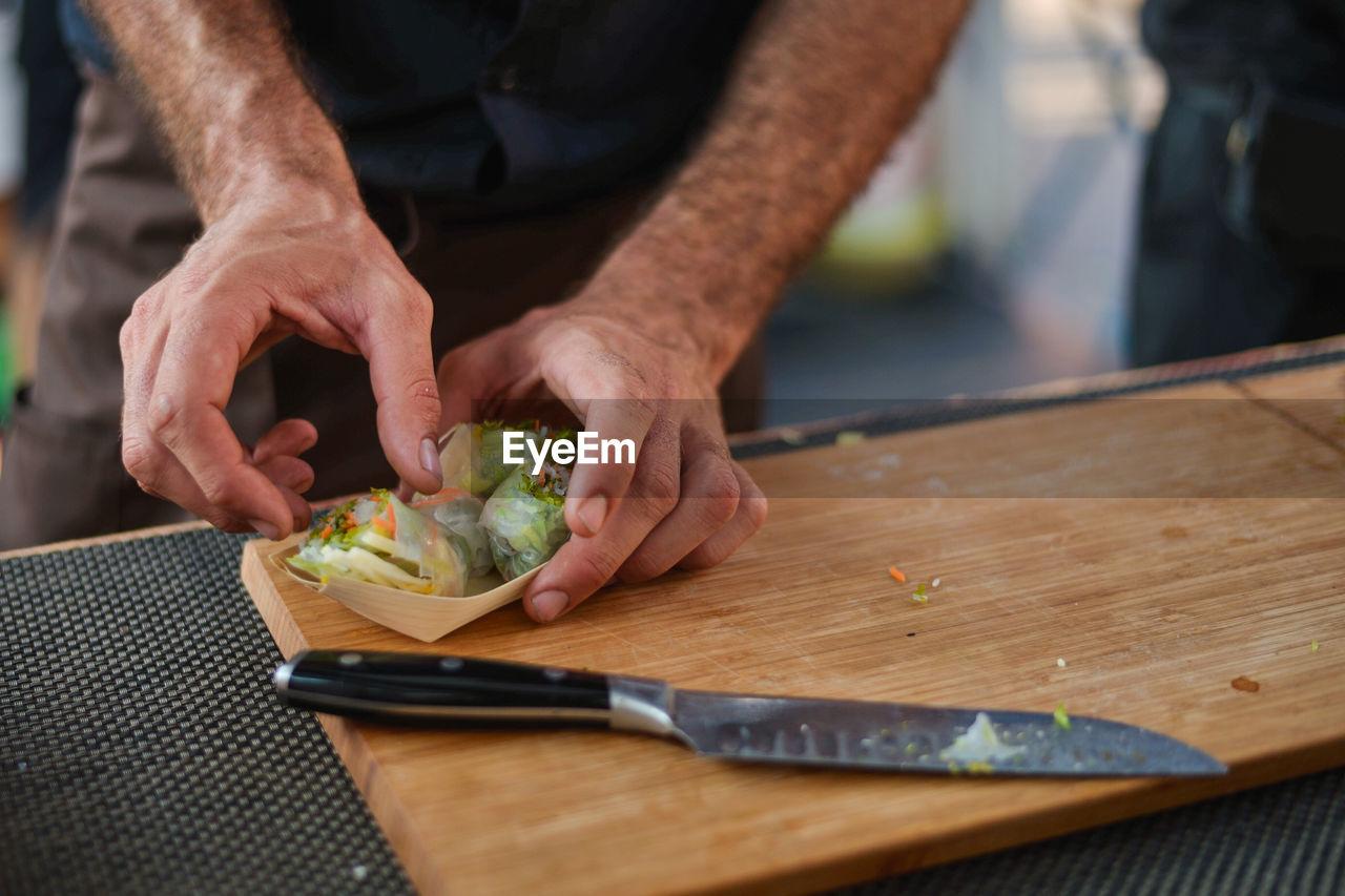 High Angle View Of Man Preparing Food At Market Stall