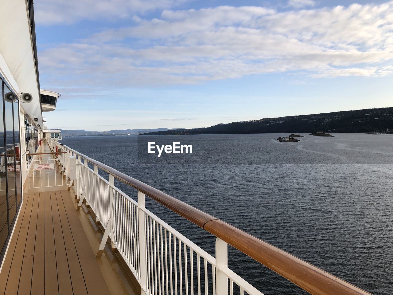 water, sky, railing, cloud - sky, sea, scenics - nature, nature, beauty in nature, transportation, day, mountain, nautical vessel, no people, tranquil scene, outdoors, mode of transportation, architecture, tranquility, built structure, cruise ship, passenger craft
