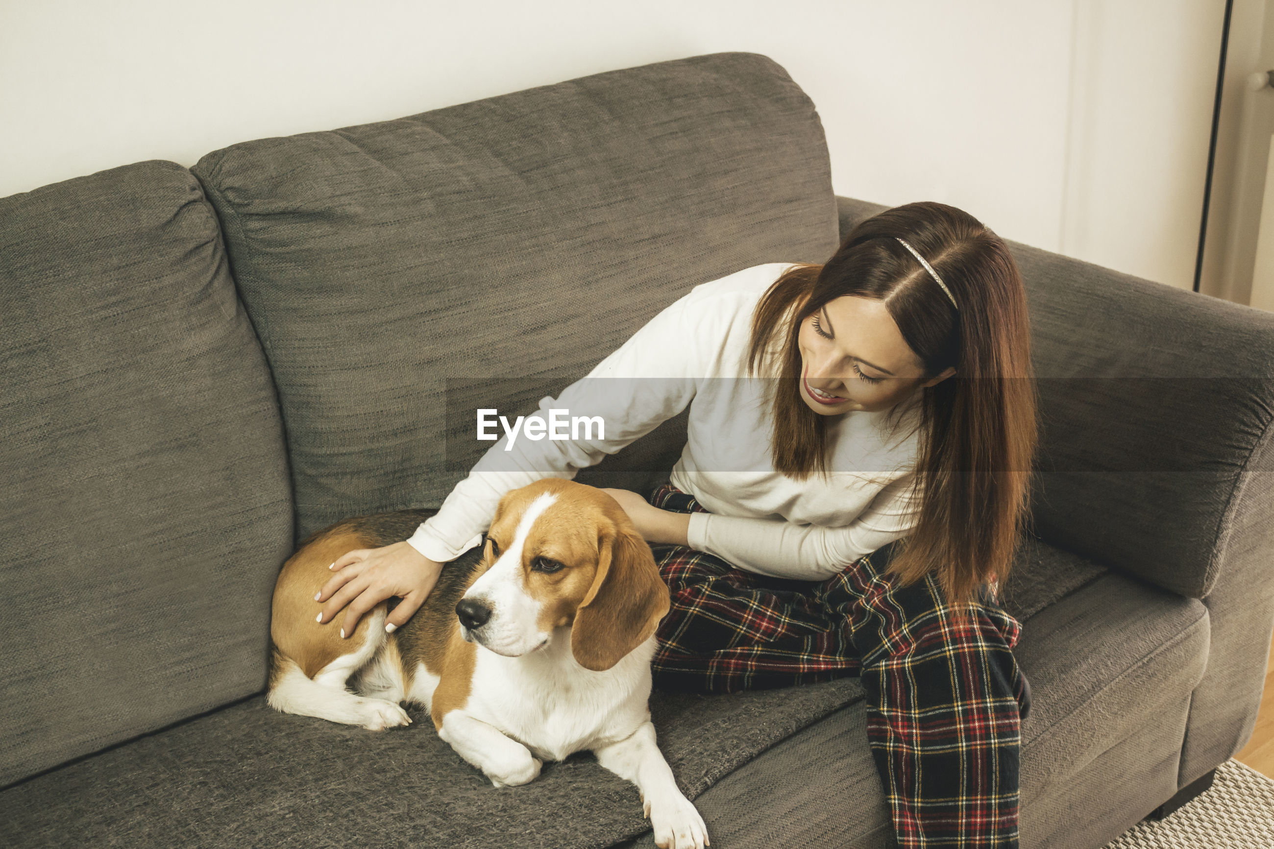 High angle view of smiling woman sitting on sofa with dog at home