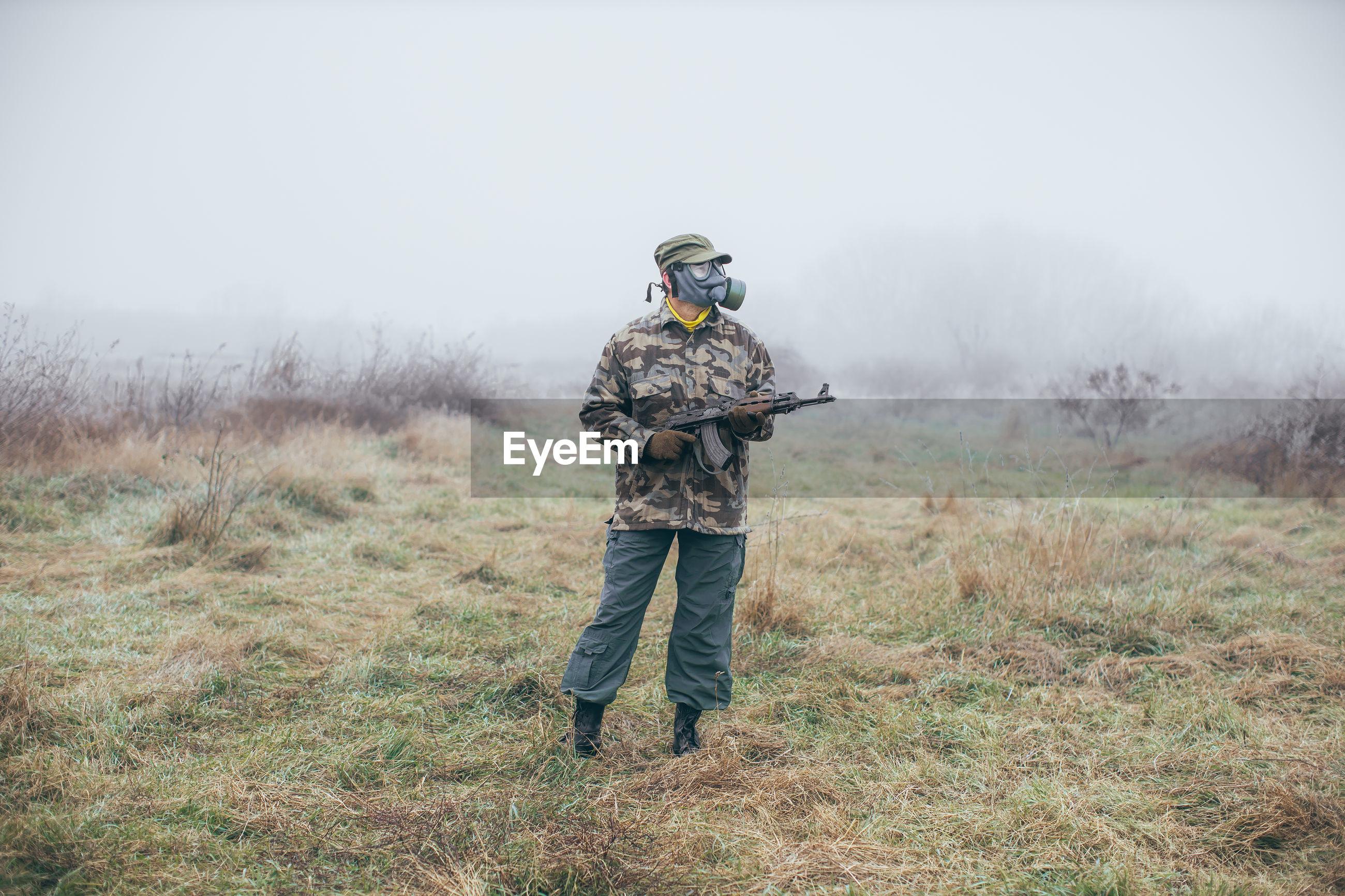 FULL LENGTH OF MAN STANDING IN FIELD