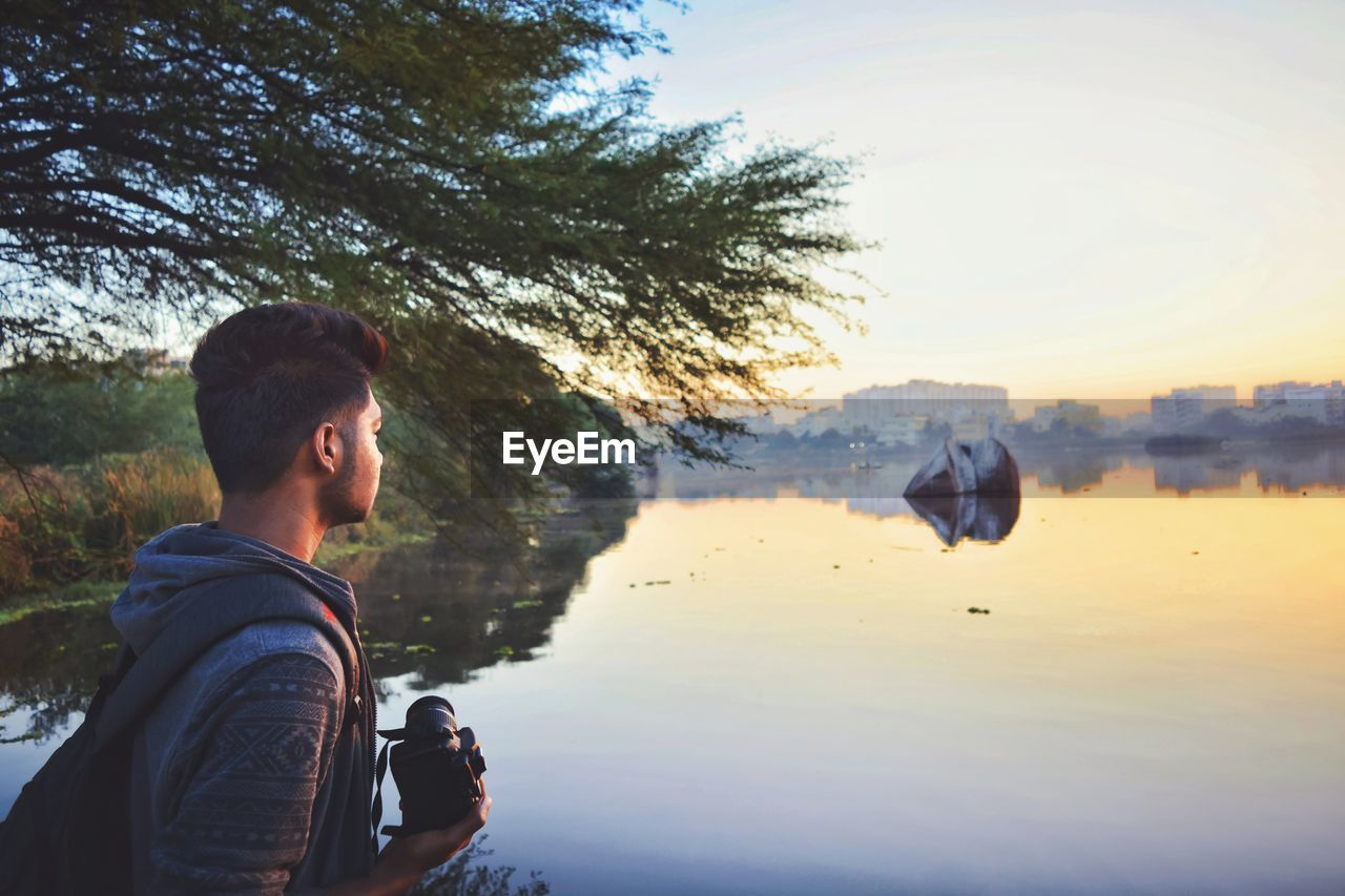 Man Holding Camera While Standing By Lake Against Sky During Sunset