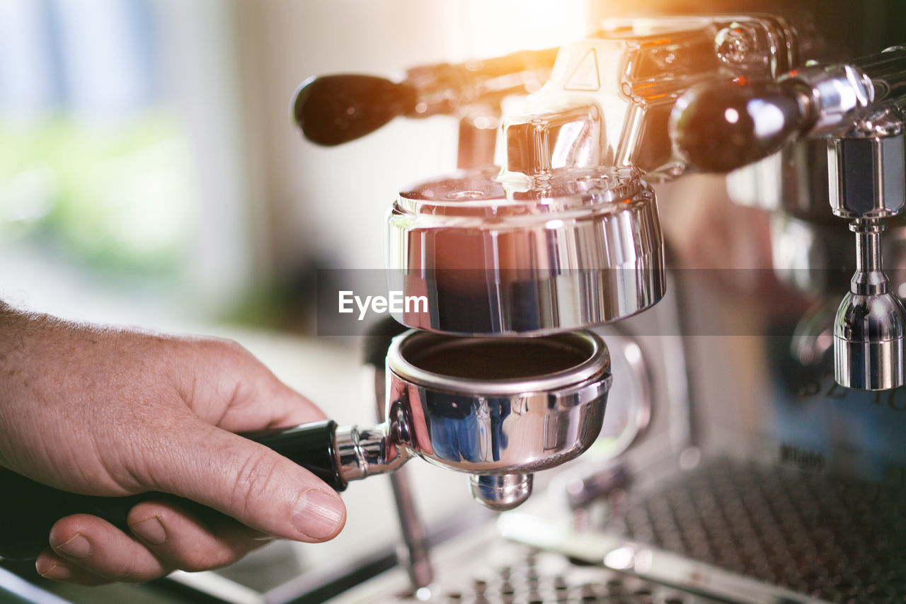 food and drink, human hand, coffee maker, drink, refreshment, making, coffee, coffee - drink, freshness, preparation, espresso maker, indoors, close-up, appliance, hand, real people, focus on foreground, machinery, one person, cafe, finger, coffee shop, barista