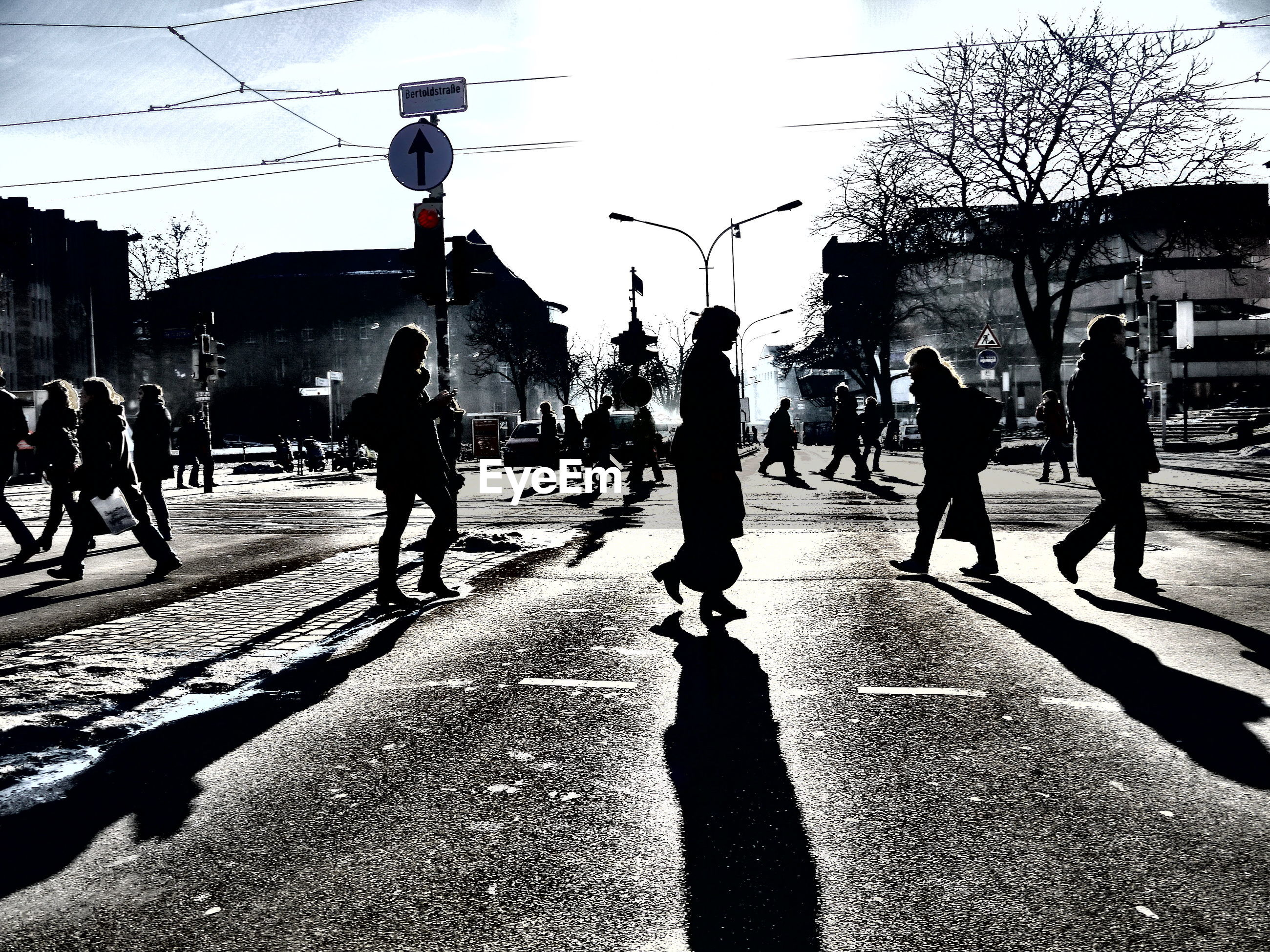 Silhouette people walking on street in city against sky