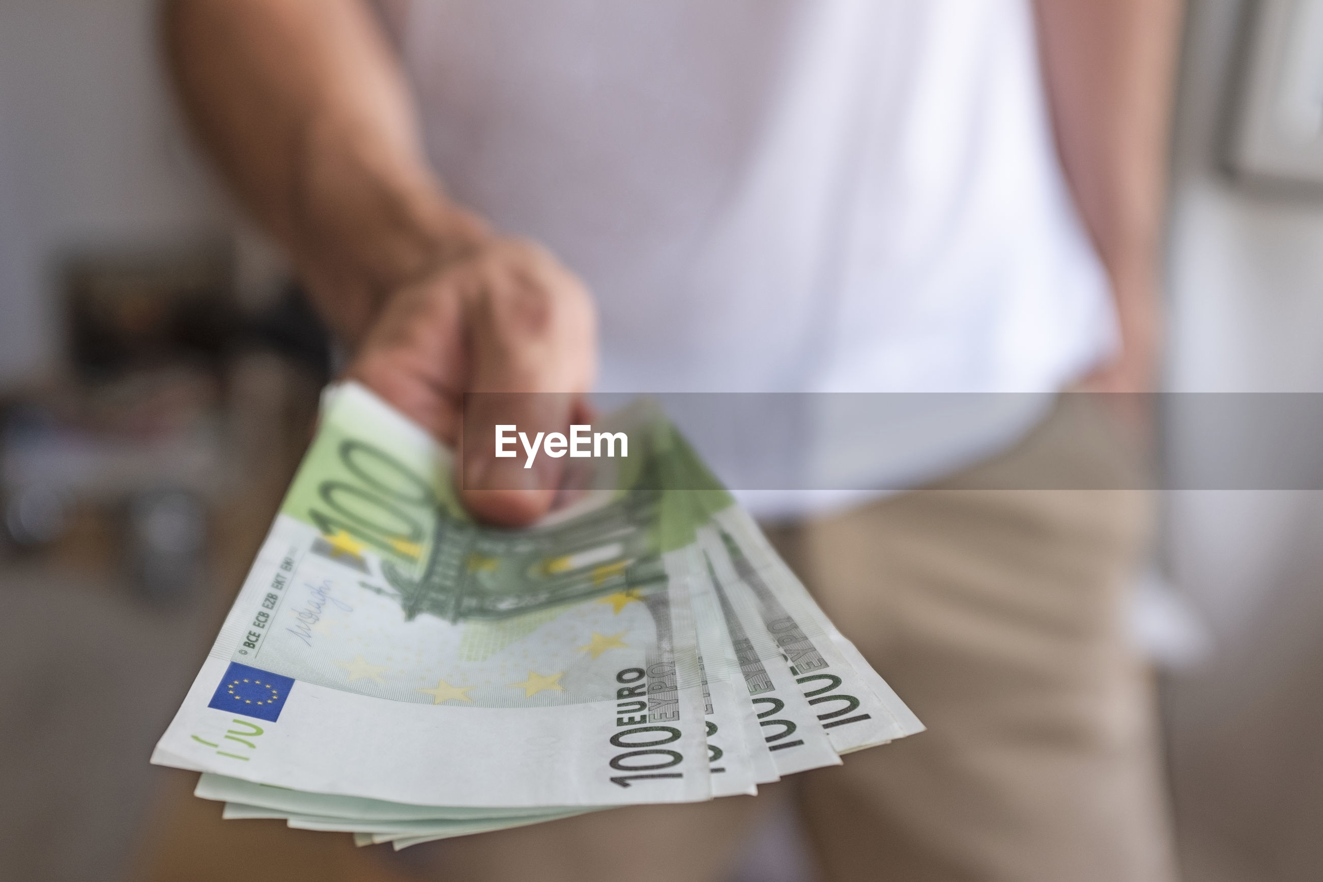 Midsection of man holding paper currency