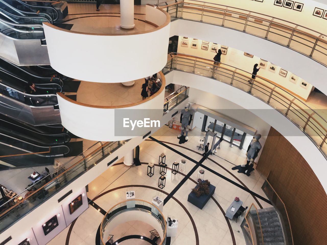 high angle view, indoors, architecture, modern, built structure, staircase, shopping mall, incidental people, day, railing, real people, technology, directly above, steps and staircases, escalator, arts culture and entertainment, building