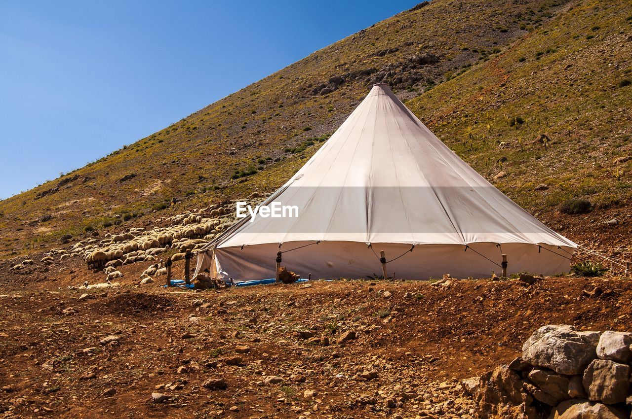 Tent on land against mountains