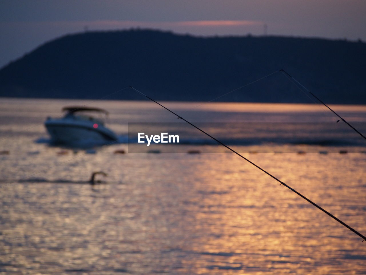 sky, water, fishing, fishing rod, sea, activity, waterfront, nature, sunset, rod, focus on foreground, nautical vessel, outdoors, beauty in nature, scenics - nature, selective focus, transportation, tranquility, real people, fisherman, fishing industry, sailboat