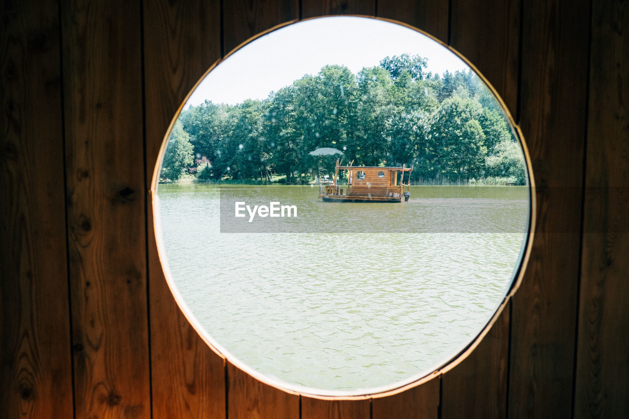 window, circle, geometric shape, water, architecture, tree, wood - material, day, nature, shape, plant, no people, built structure, outdoors, sky, transparent, reflection, glass - material