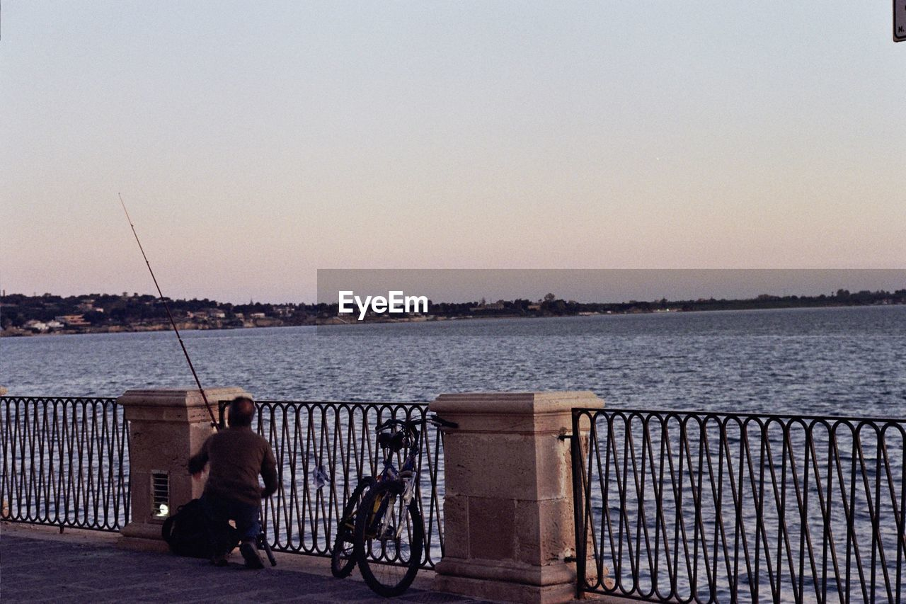 sky, water, real people, railing, sea, transportation, copy space, lifestyles, men, bicycle, clear sky, nature, activity, leisure activity, people, fishing rod, rear view, full length, outdoors, promenade