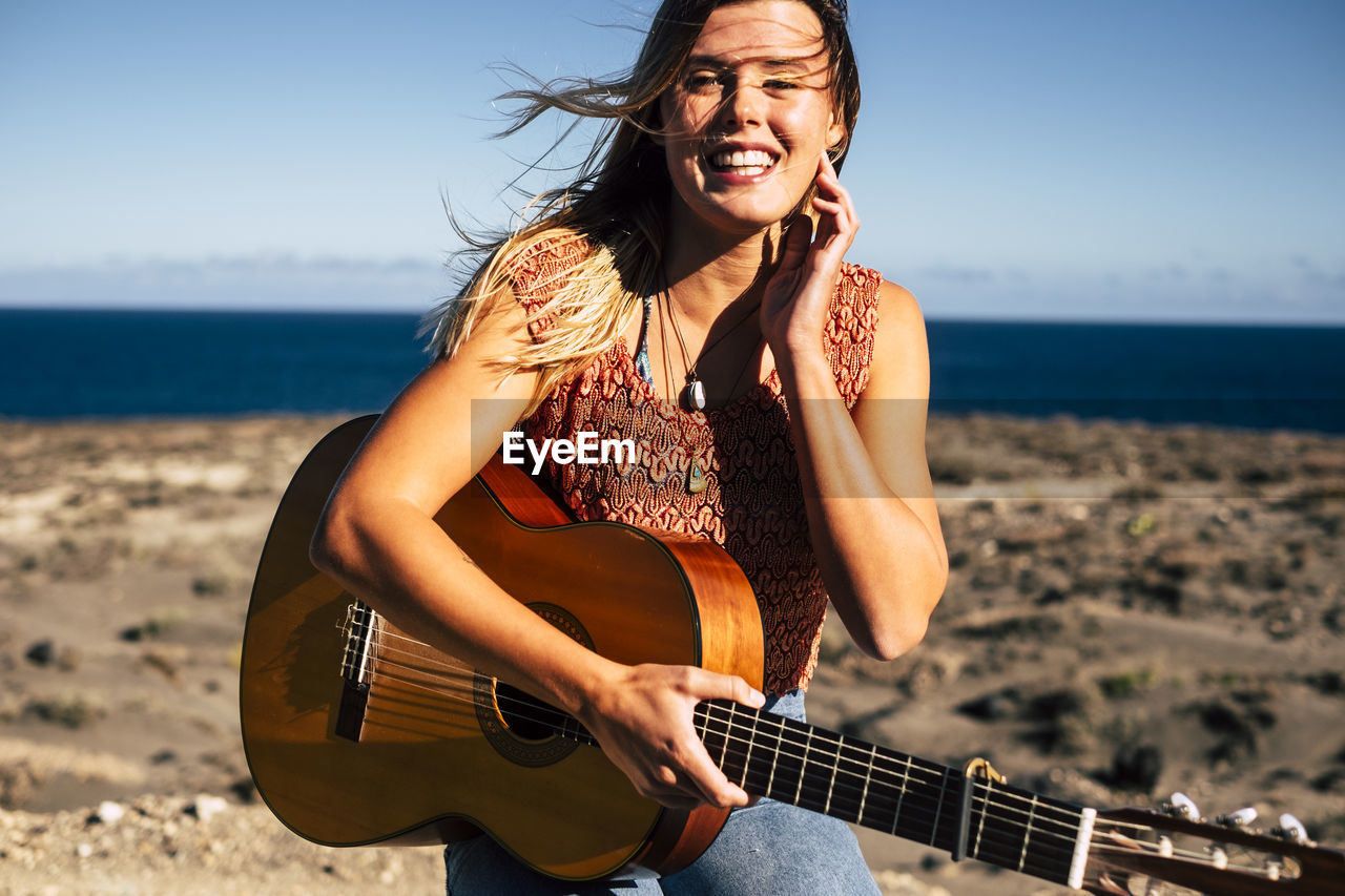 Portrait Of Young Woman With Guitar At Beach