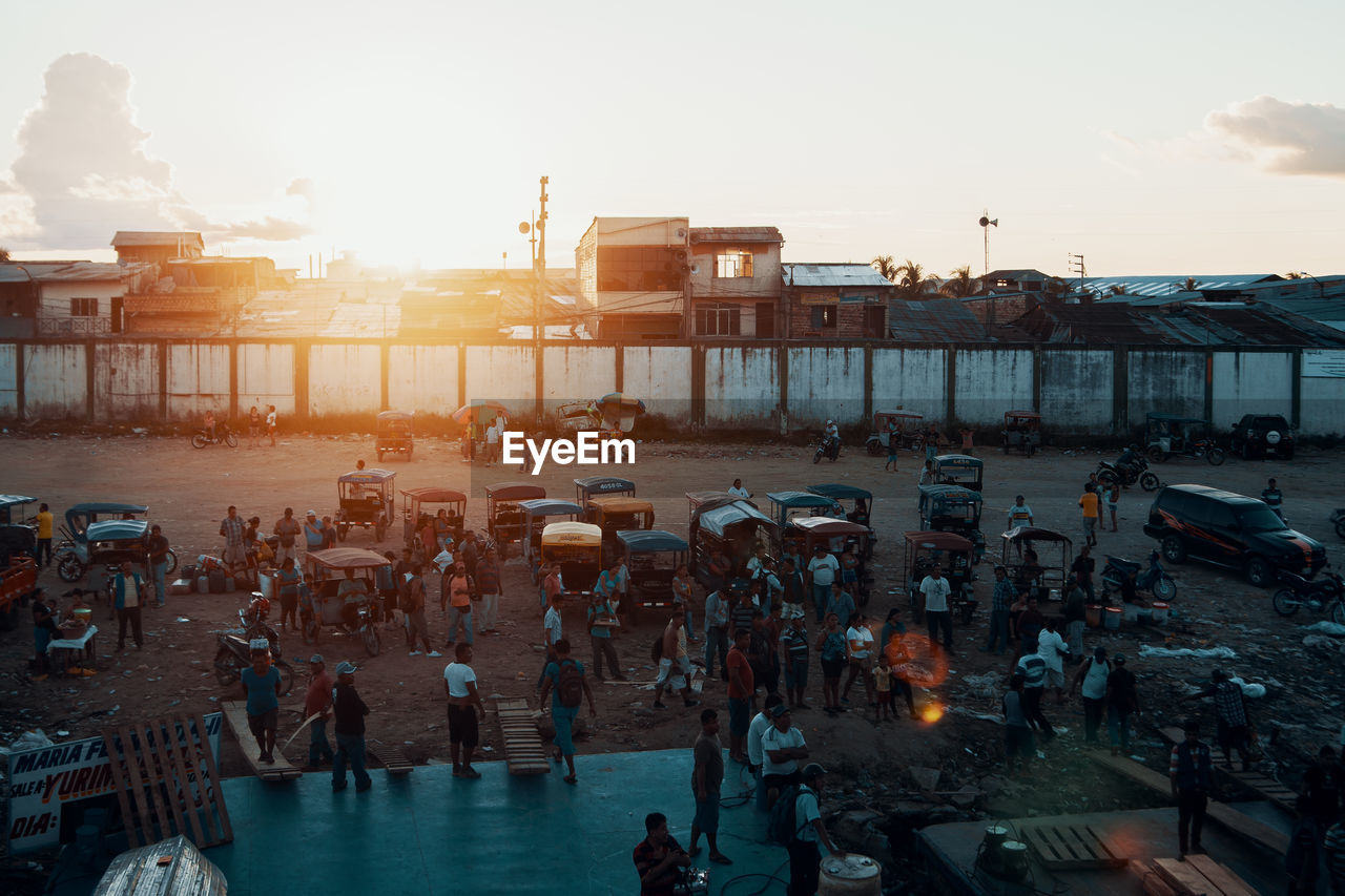 sky, group of people, architecture, crowd, building exterior, large group of people, nature, built structure, real people, high angle view, sunset, water, city, transportation, mode of transportation, sun, travel, lifestyles, outdoors, lens flare, bright
