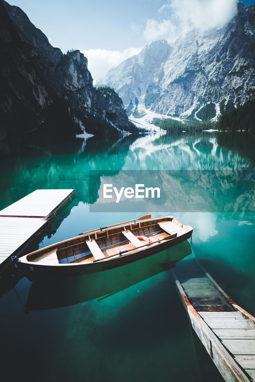 water, mountain, nautical vessel, scenics - nature, beauty in nature, transportation, nature, mode of transportation, day, lake, tranquility, mountain range, no people, tranquil scene, non-urban scene, sky, moored, wood - material, reflection, rowboat, swimming pool