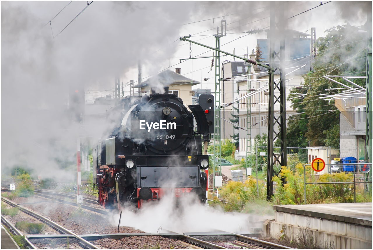 rail transportation, smoke - physical structure, train - vehicle, train, steam train, railroad track, track, public transportation, transportation, mode of transportation, locomotive, steam, day, nature, motion, land vehicle, outdoors, passenger train, architecture, emitting, shunting yard