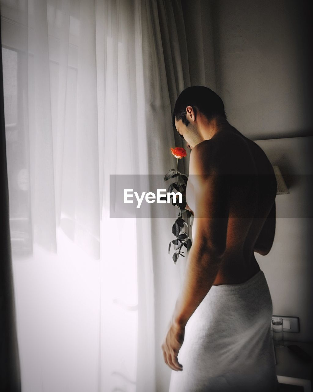 Shirtless Young Man Holding Rose While Standing By Curtain At Home