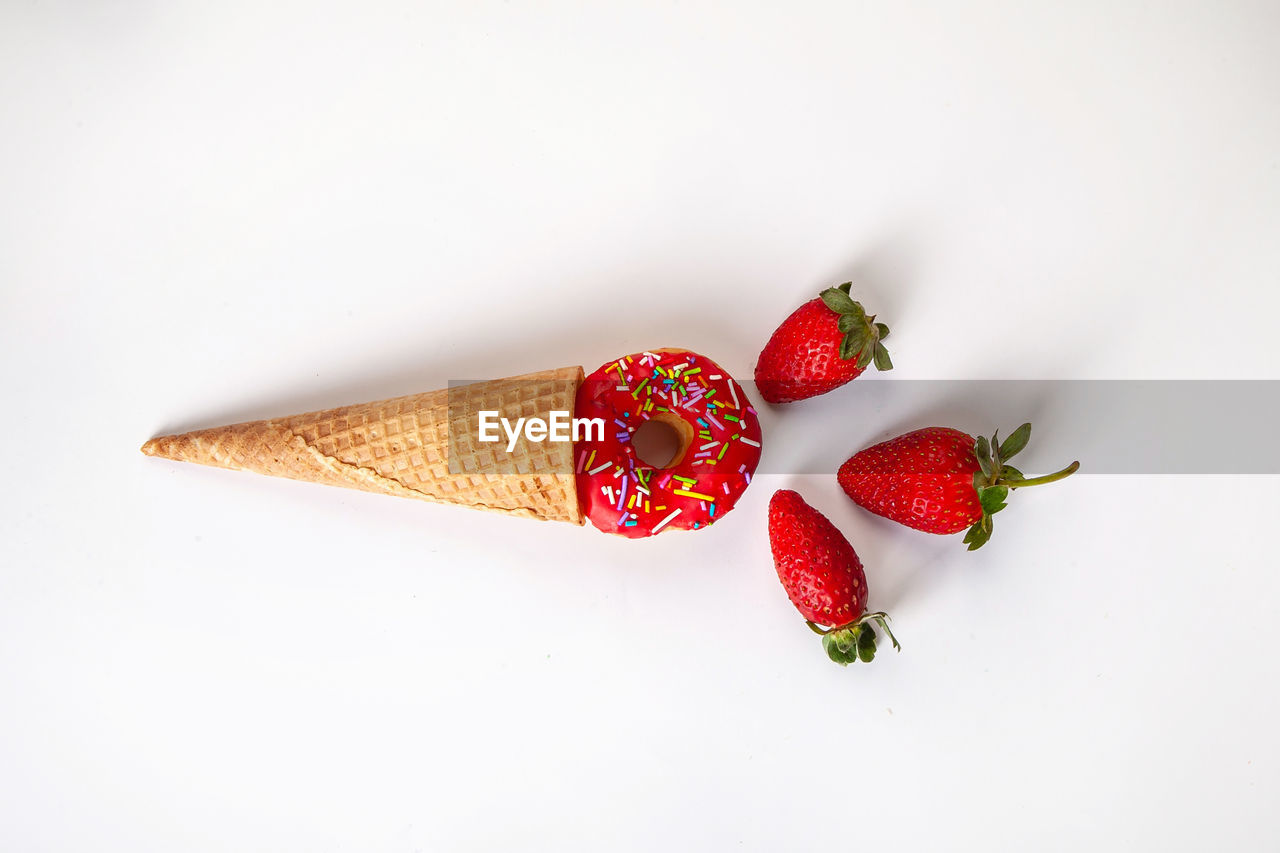 HIGH ANGLE VIEW OF STRAWBERRIES ON WHITE TABLE