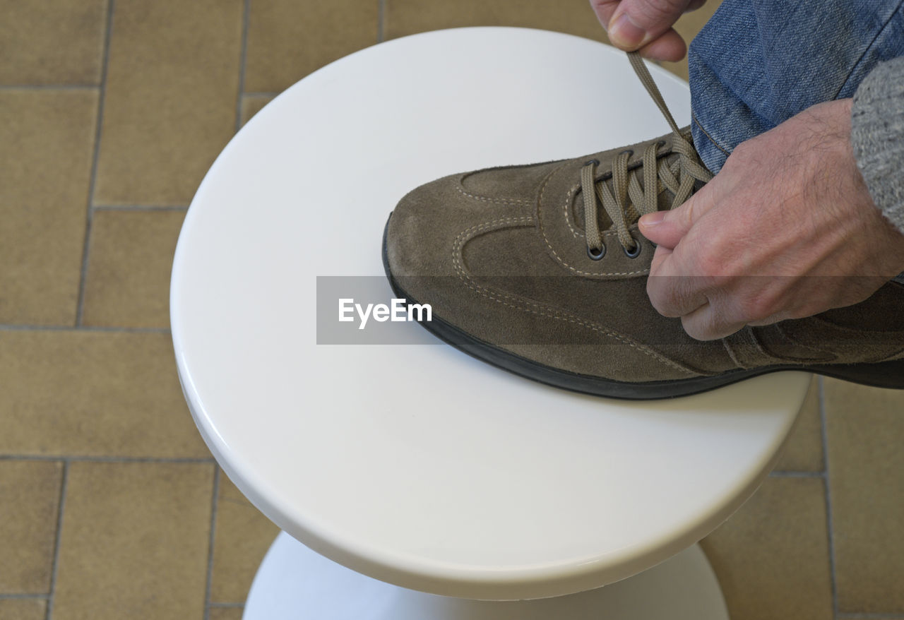 Low section of man tying shoelace on stool at home