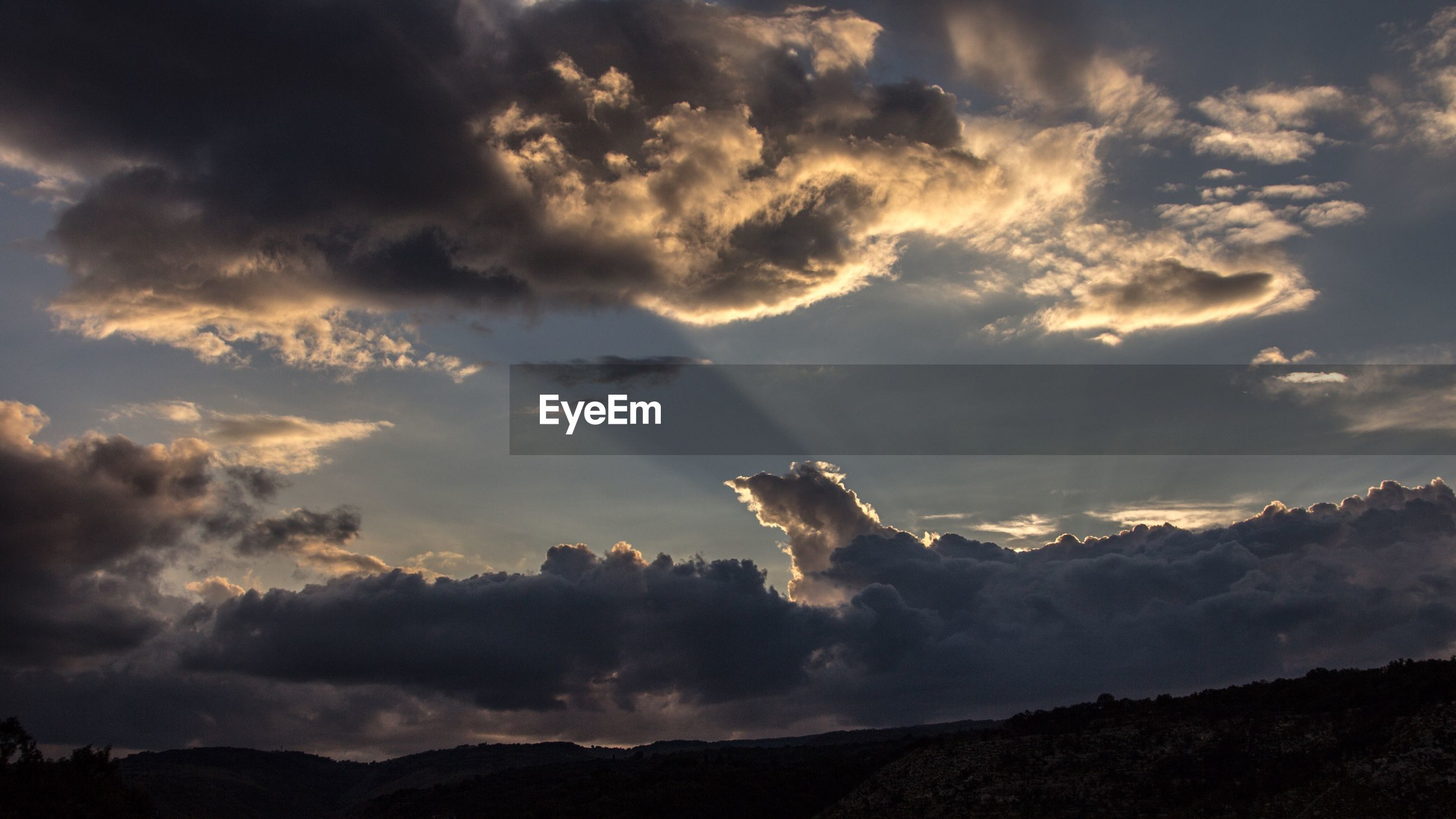 LOW ANGLE VIEW OF DRAMATIC SKY OVER SILHOUETTE MOUNTAIN