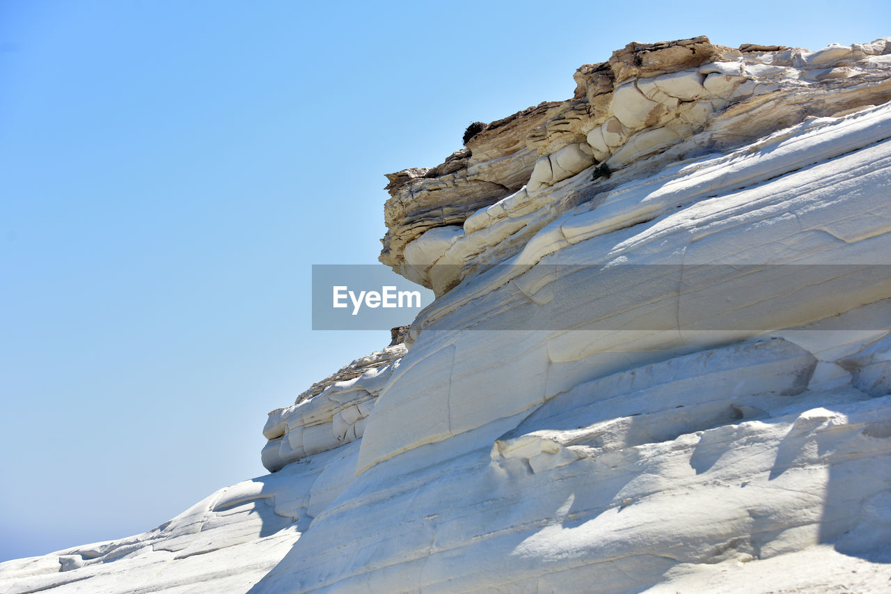 winter, cold temperature, low angle view, snow, nature, sunlight, day, outdoors, rock - object, clear sky, no people, mountain, blue, beauty in nature, scenics, sky