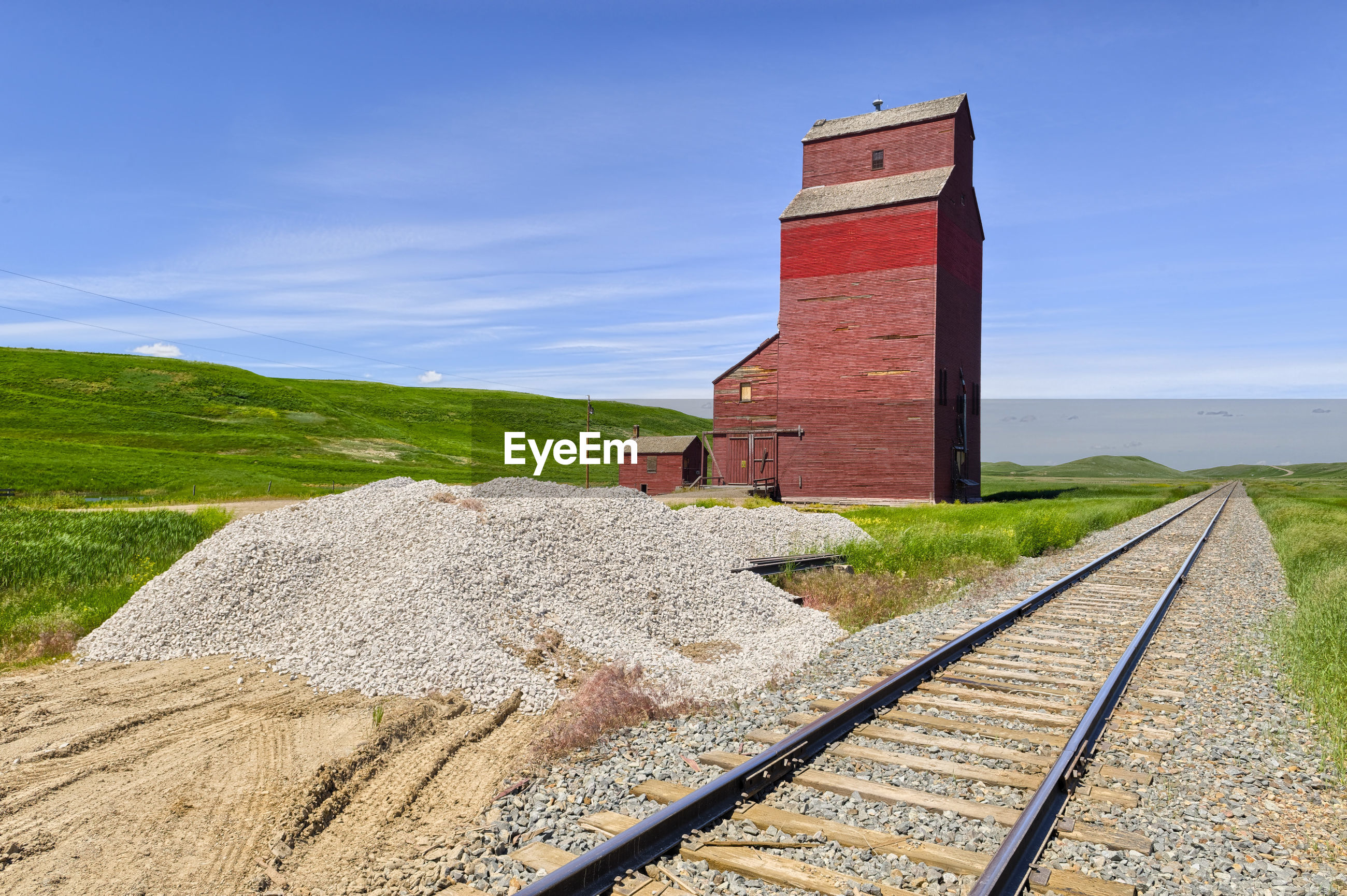 Railroad tracks by house on field against sky