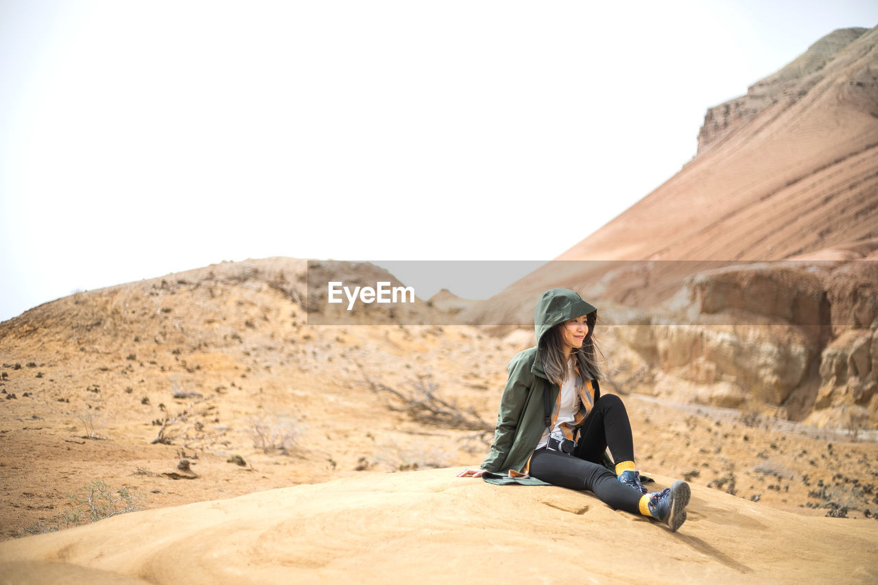 one person, leisure activity, lifestyles, sitting, sky, full length, rock, clear sky, real people, copy space, young adult, solid, rock - object, nature, relaxation, mountain, casual clothing, land, scenics - nature, climate, arid climate