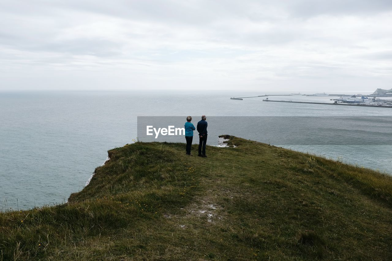 Rear view of senior couple standing on cliff by sea against sky