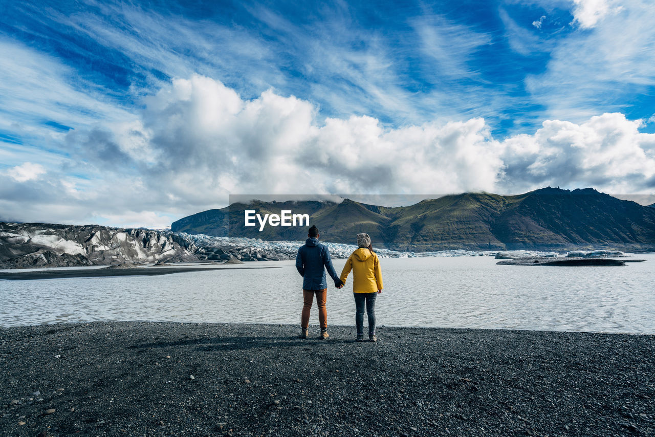 Rear view of two people on beach against sky