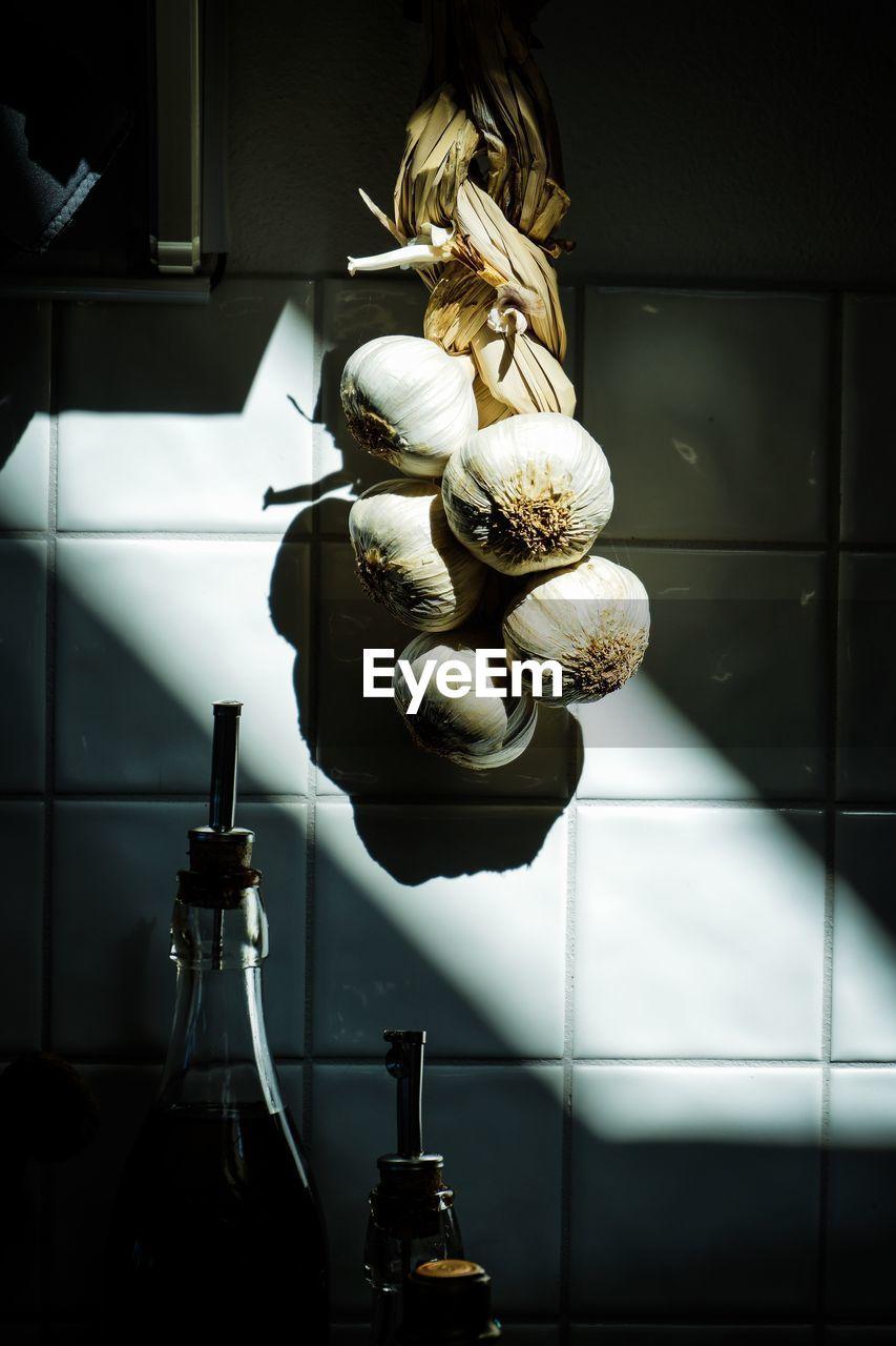 Close-up of garlic hanging on wall at home