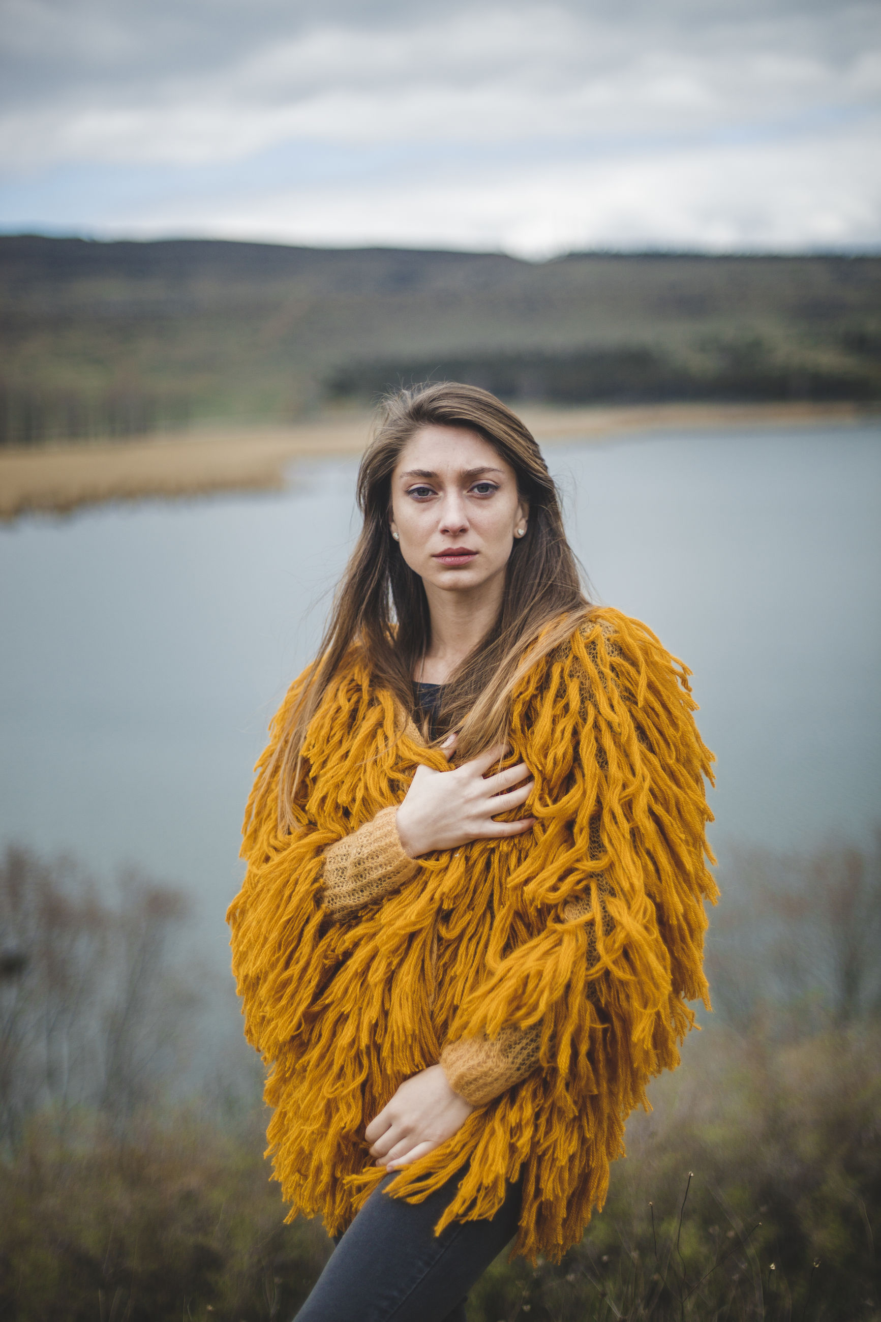 Portrait of woman in warm clothing standing against lake