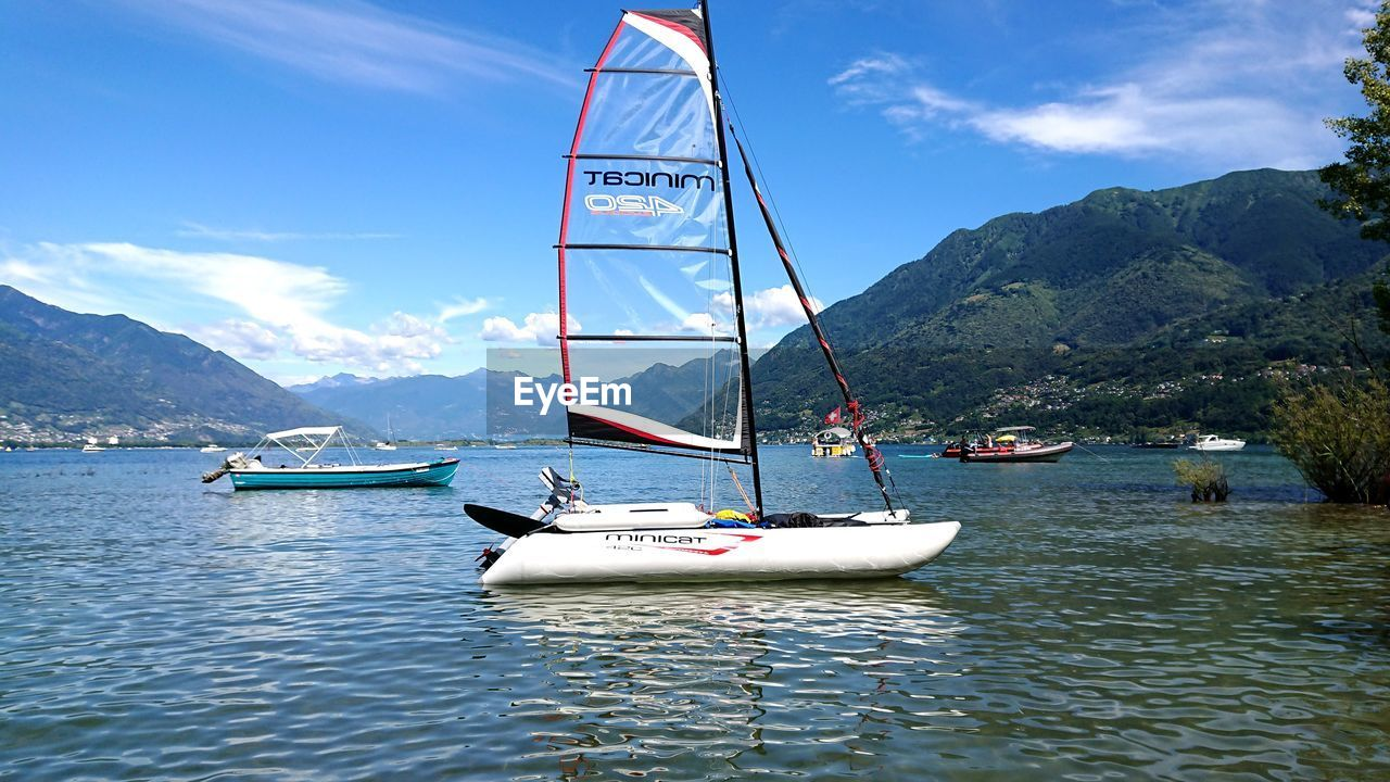 water, nautical vessel, transportation, mode of transportation, mountain, sea, sky, day, nature, waterfront, sailboat, cloud - sky, beauty in nature, scenics - nature, moored, non-urban scene, incidental people, outdoors, mountain range, yacht