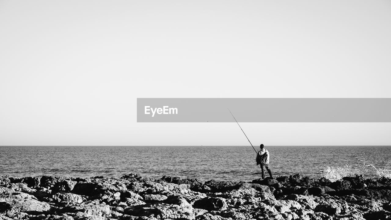 sea, water, sky, horizon, horizon over water, real people, rod, scenics - nature, copy space, leisure activity, clear sky, fishing rod, nature, fishing, men, beauty in nature, day, lifestyles, land, outdoors, fisherman