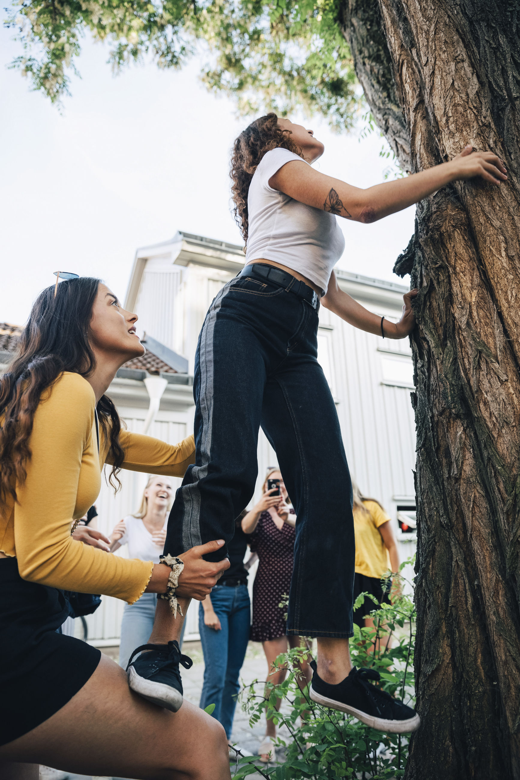 WOMAN STANDING BY PEOPLE IN A TREE