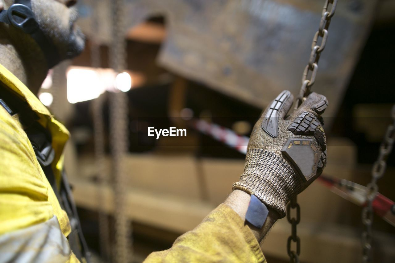 Midsection of engineer holding chain at construction site