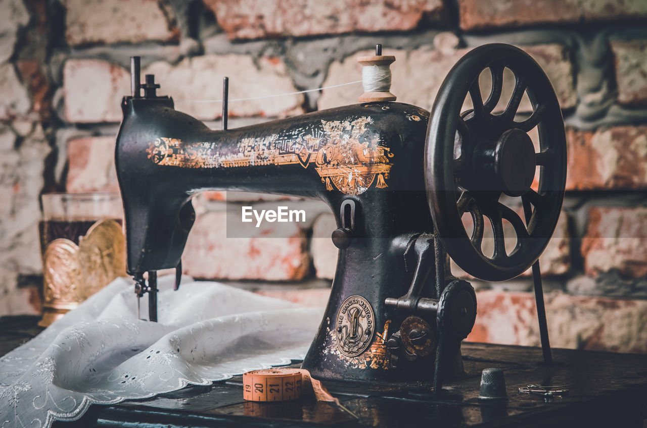 Close-Up Of Sewing Machine Against Brick Wall