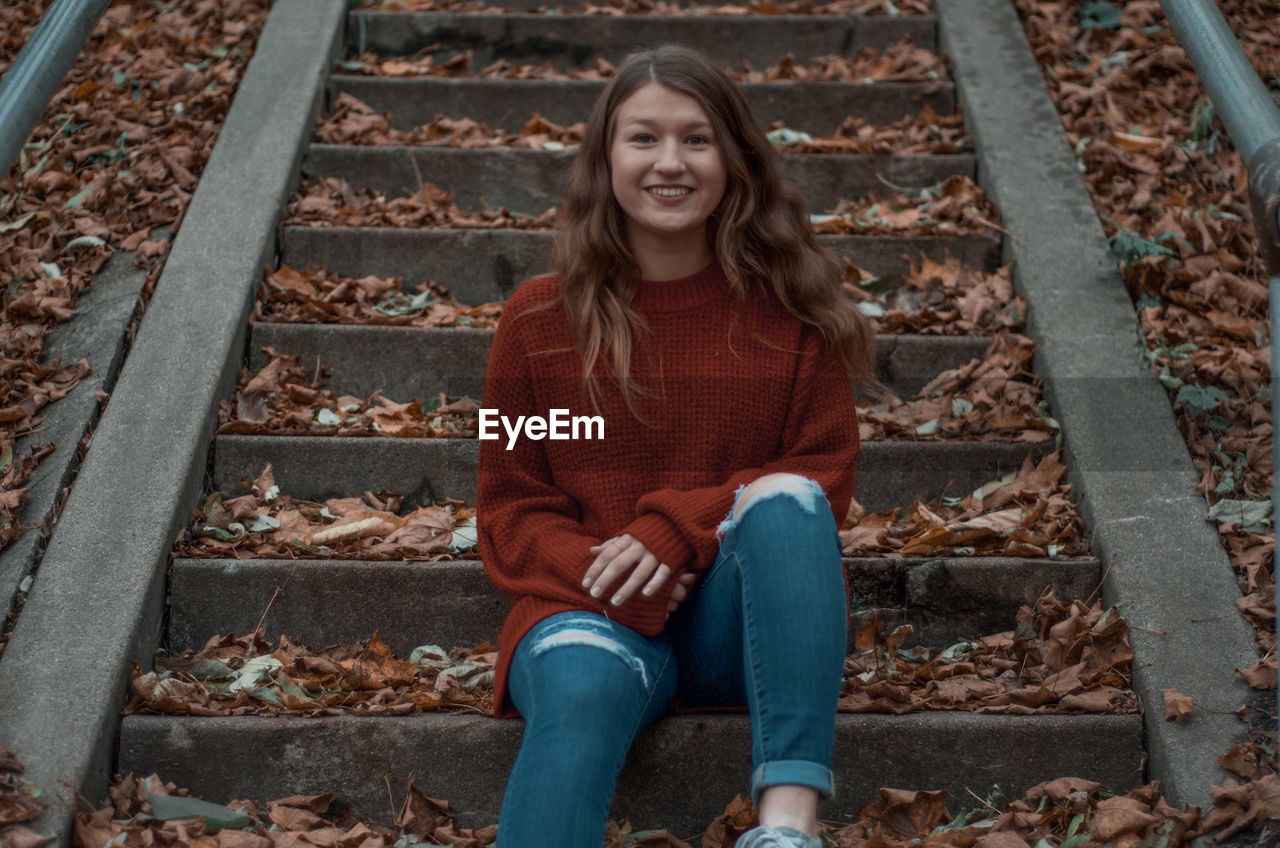 Portrait of a smiling girl sitting on staircase outdoors