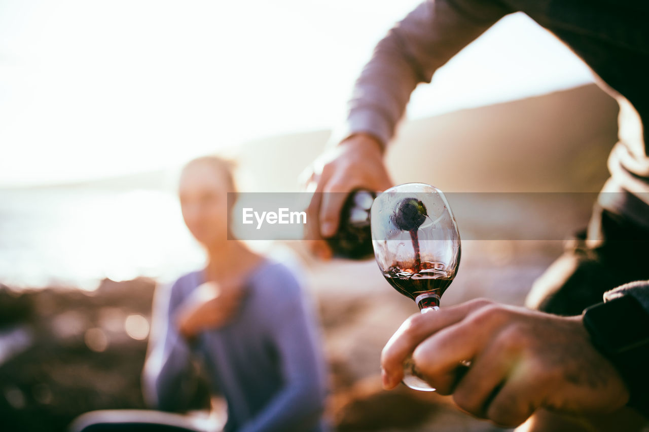 Midsection Of Man Pouring Red Wine While Woman Sitting In Background During Sunset