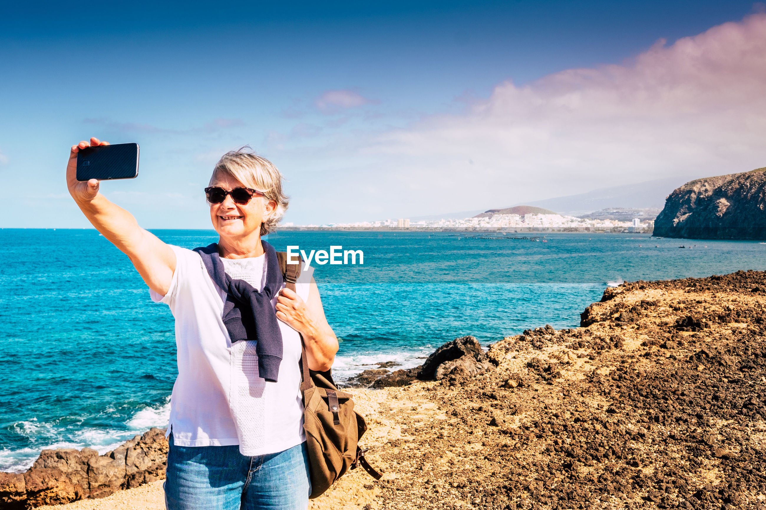 Senior woman taking selfie with smart phone while standing at beach against sky during sunny day