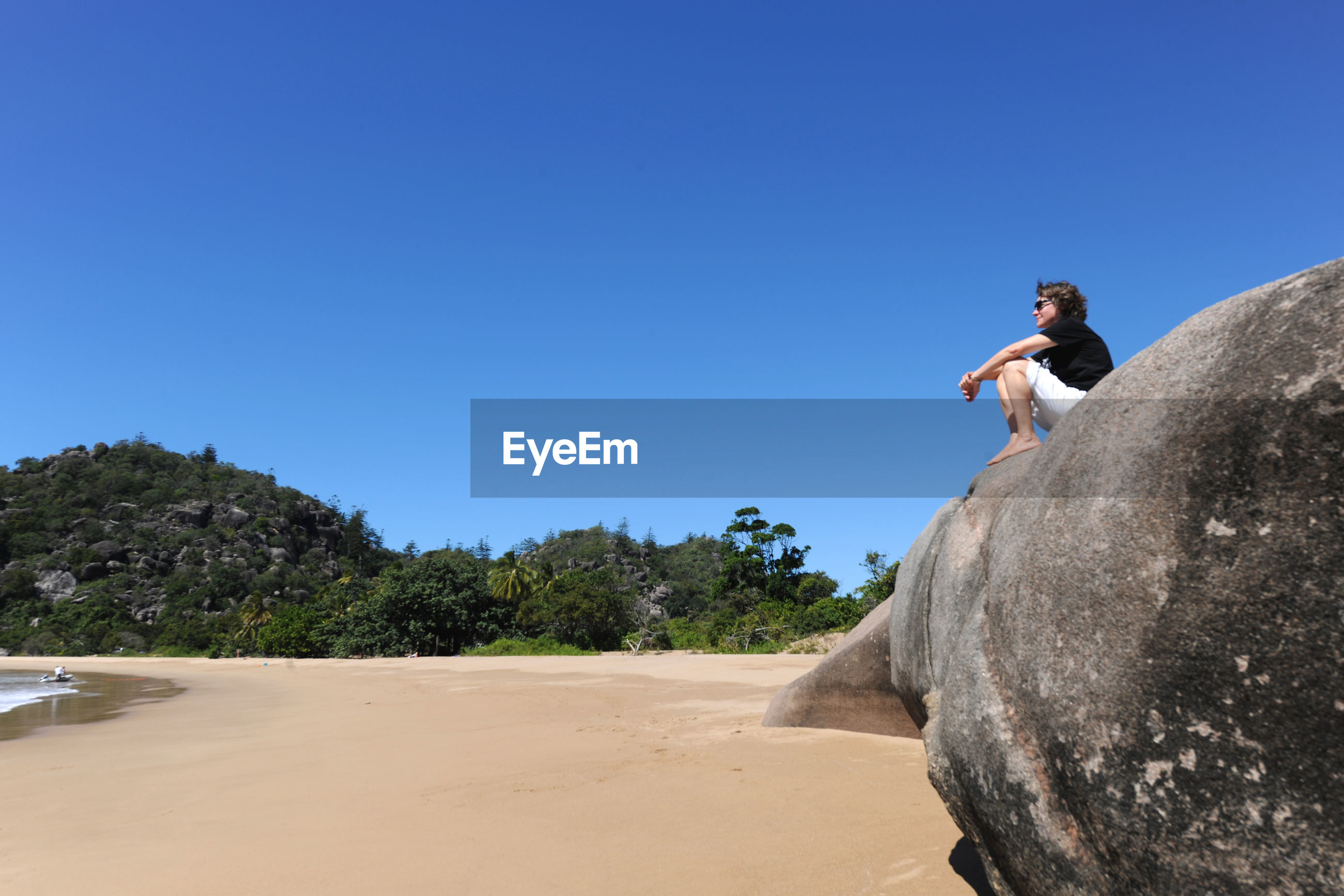Low angle view of woman sitting on boulder at beach against clear blue sky