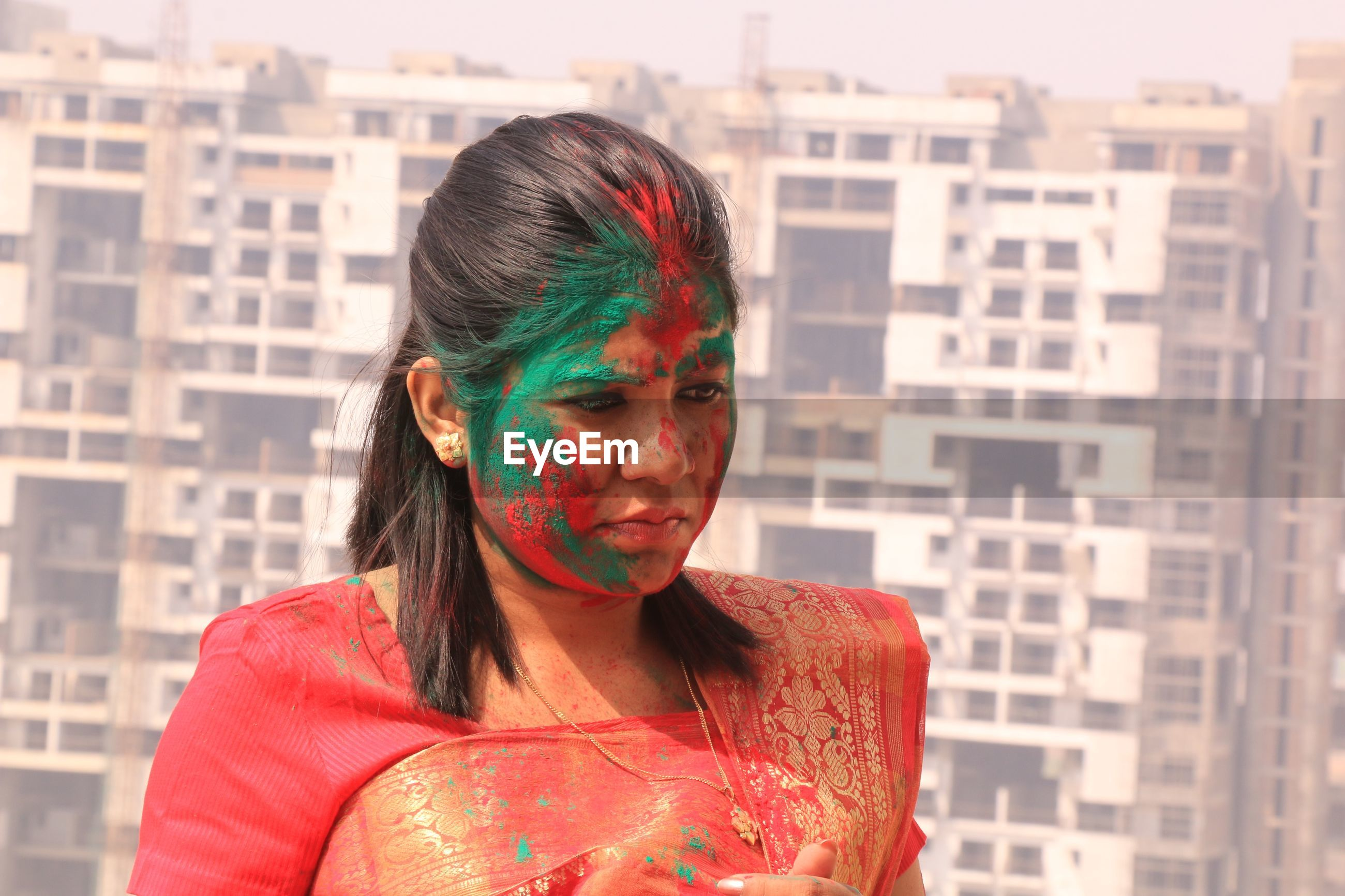 Close-up of young woman with powder paint on face during holi in city