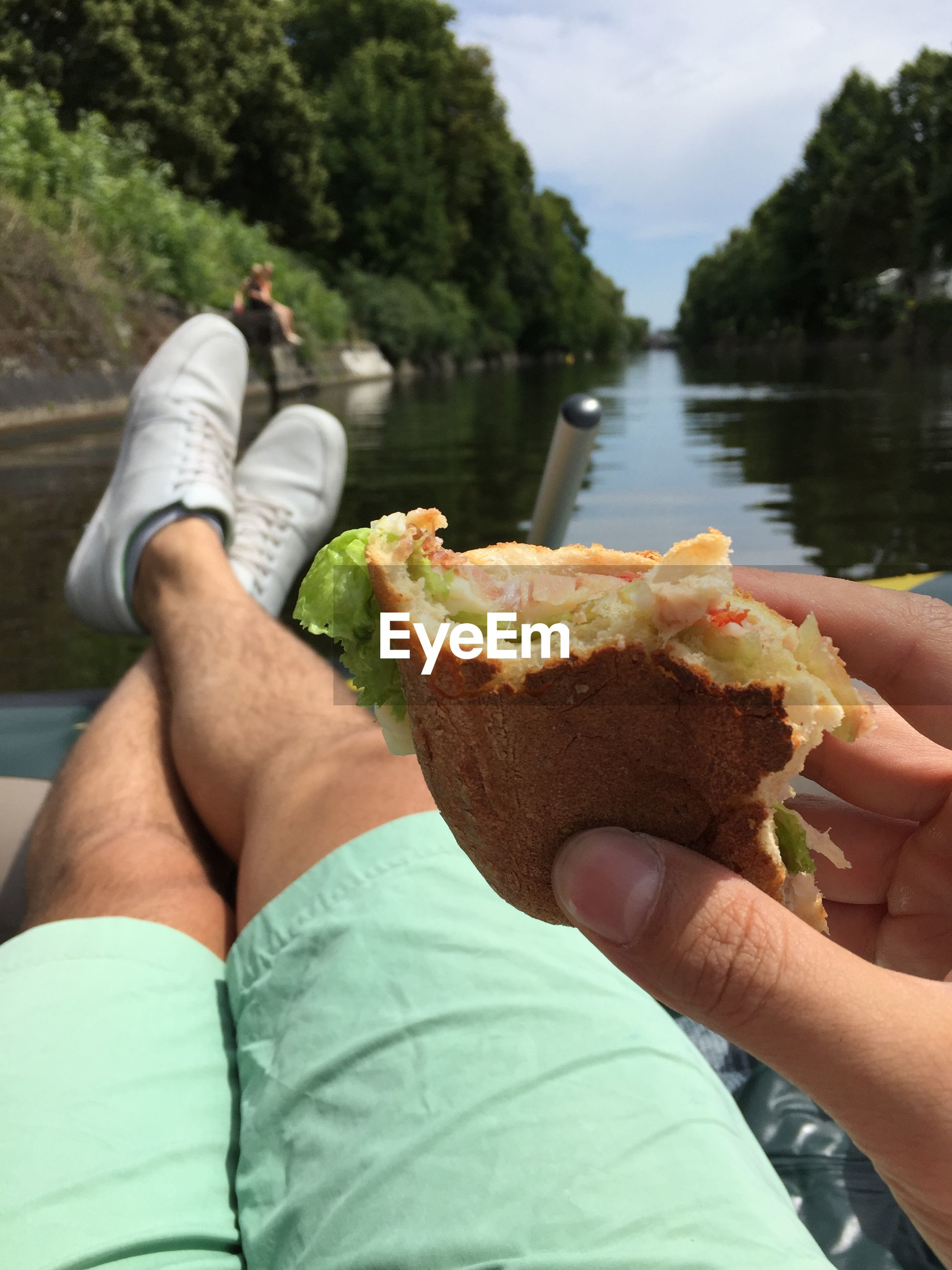 Cropped image of man eating sandwich against lake