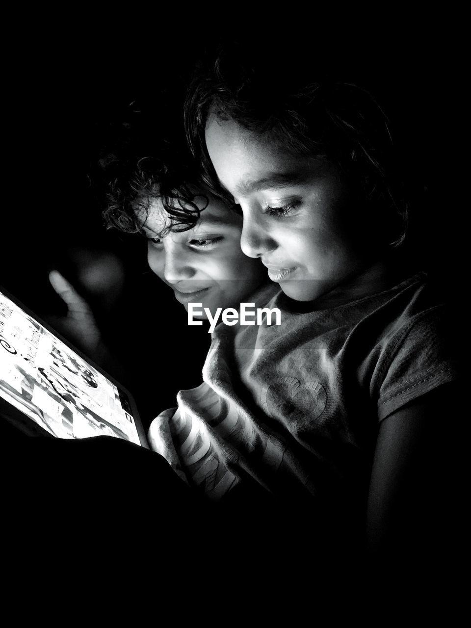 Smiling Cute Siblings Playing On Digital Tablet In Darkroom