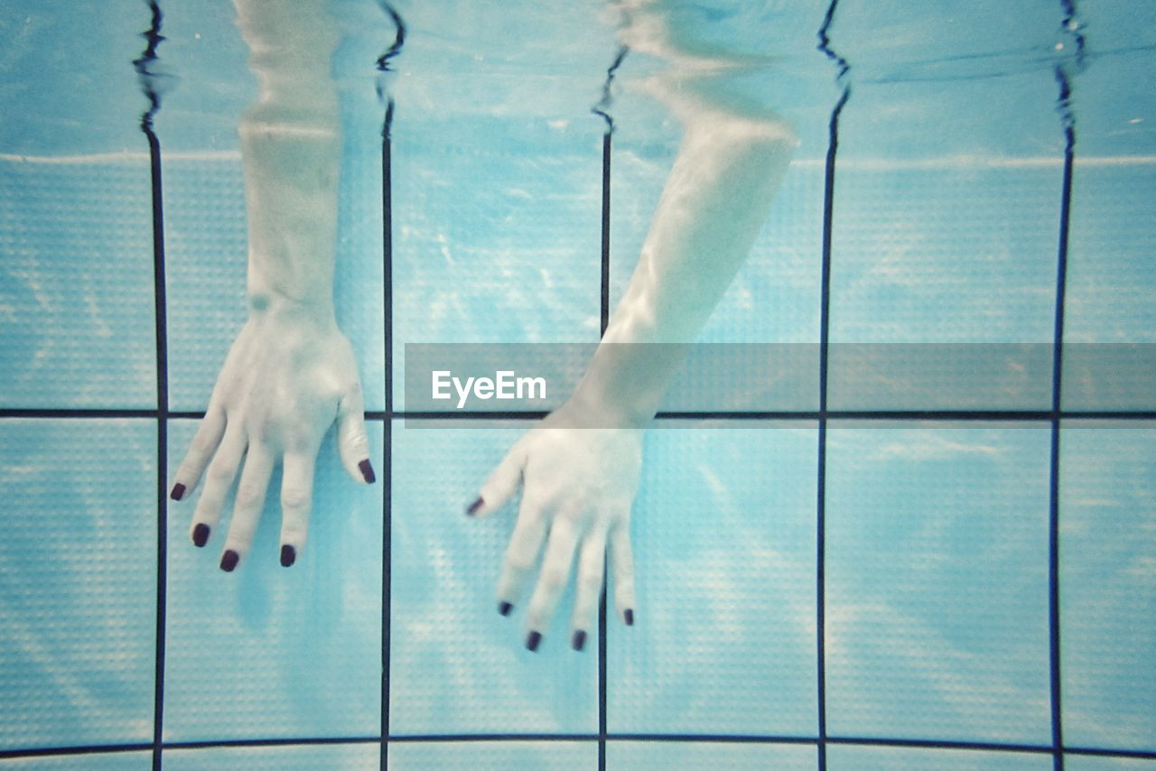 Close-Up Of Hands With Nail Polish Dipped In Swimming Pool