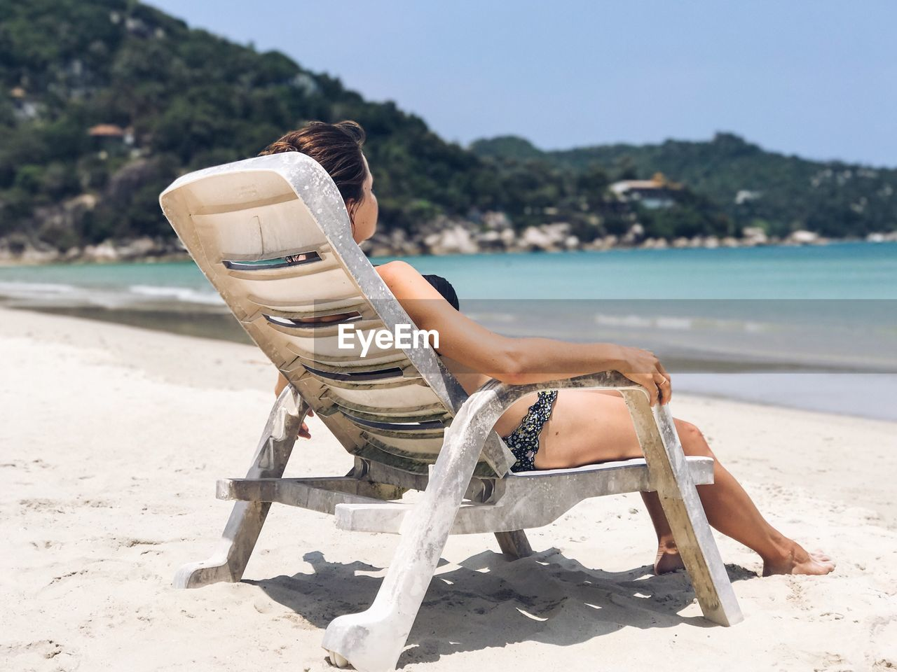 Low Section Of Woman Sitting On Beach
