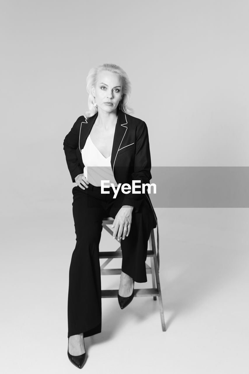 Full length portrait of businesswoman sitting on stool over gray background