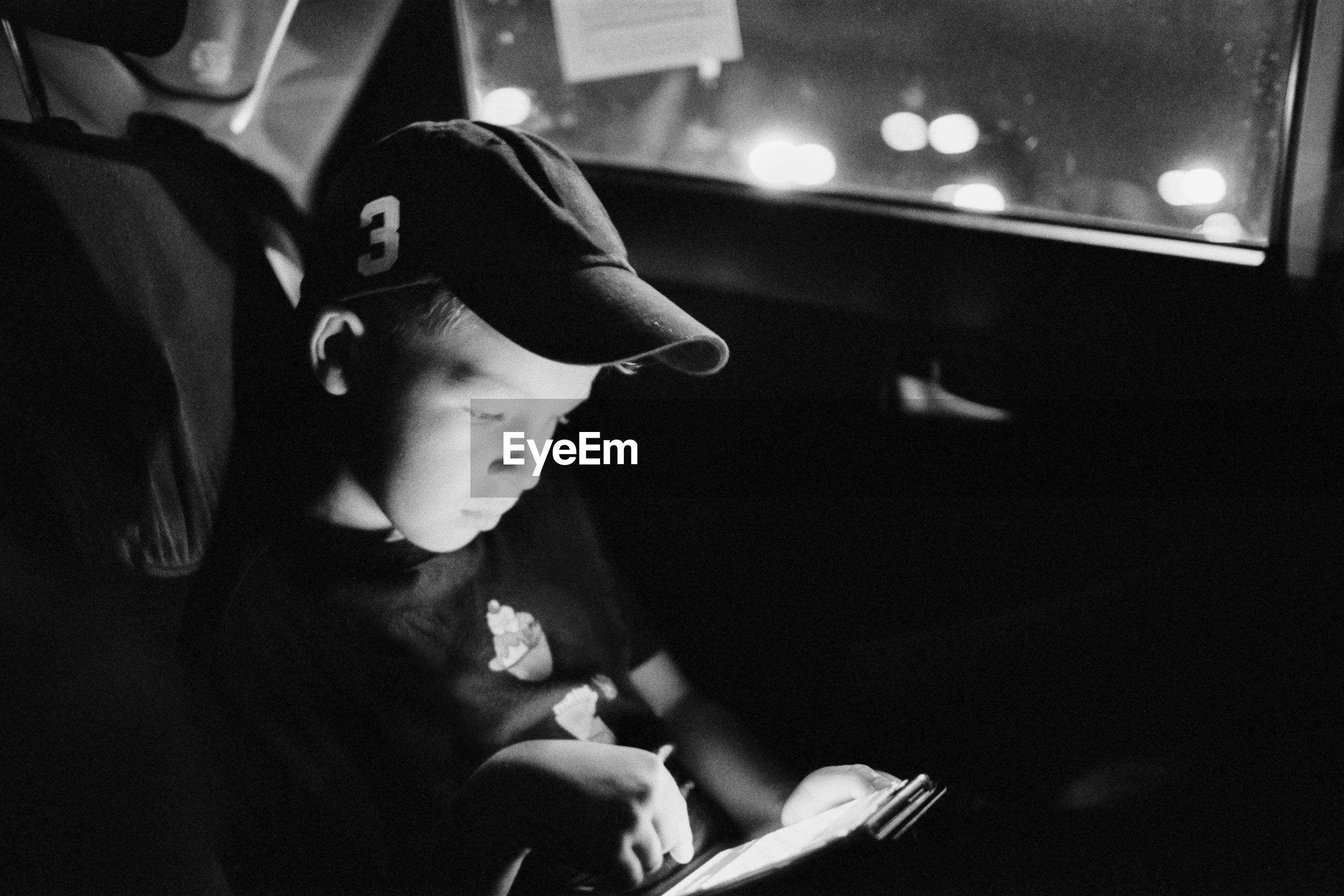 Boy wearing cap while using smart phone in car at night